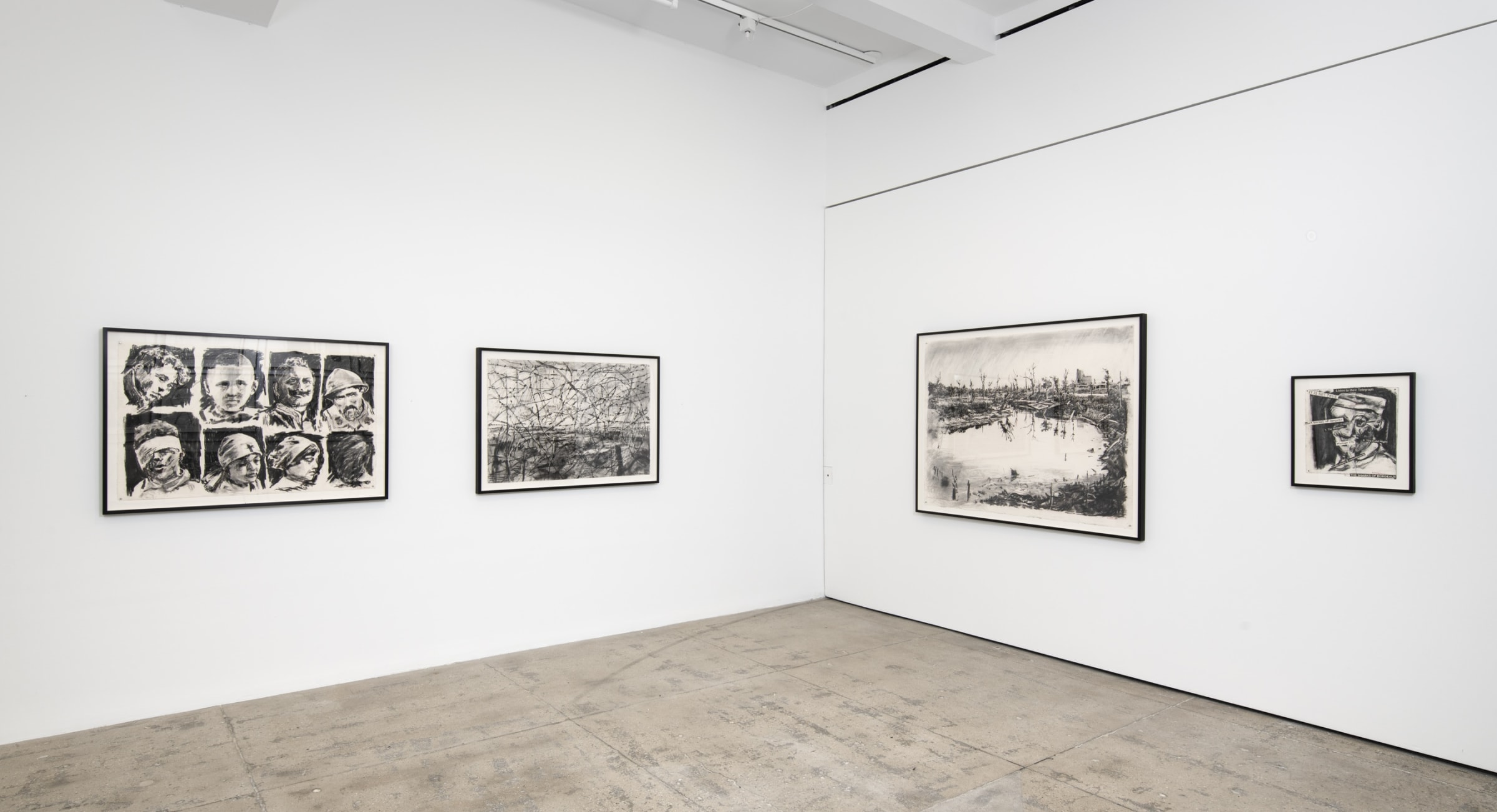 Four graphite drawings of battered children and war-torn landscapes hang in the corner of a room.