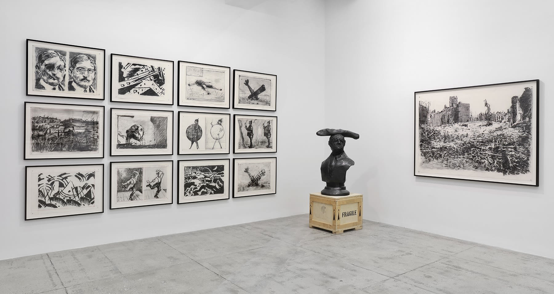 A copper sculpture of the bust of an unknown man stands between graphite drawings of war-torn landscapes, crashing airplanes, dancing men and injured figures.