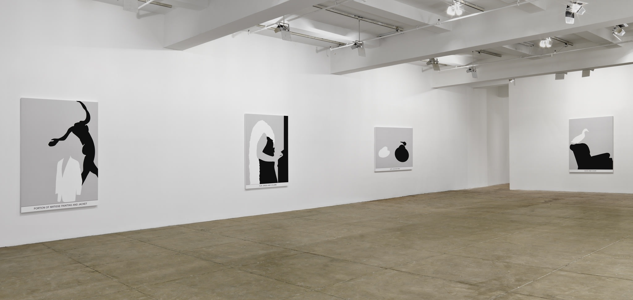 Four black and white paintings hang in a white space with a beige floor.