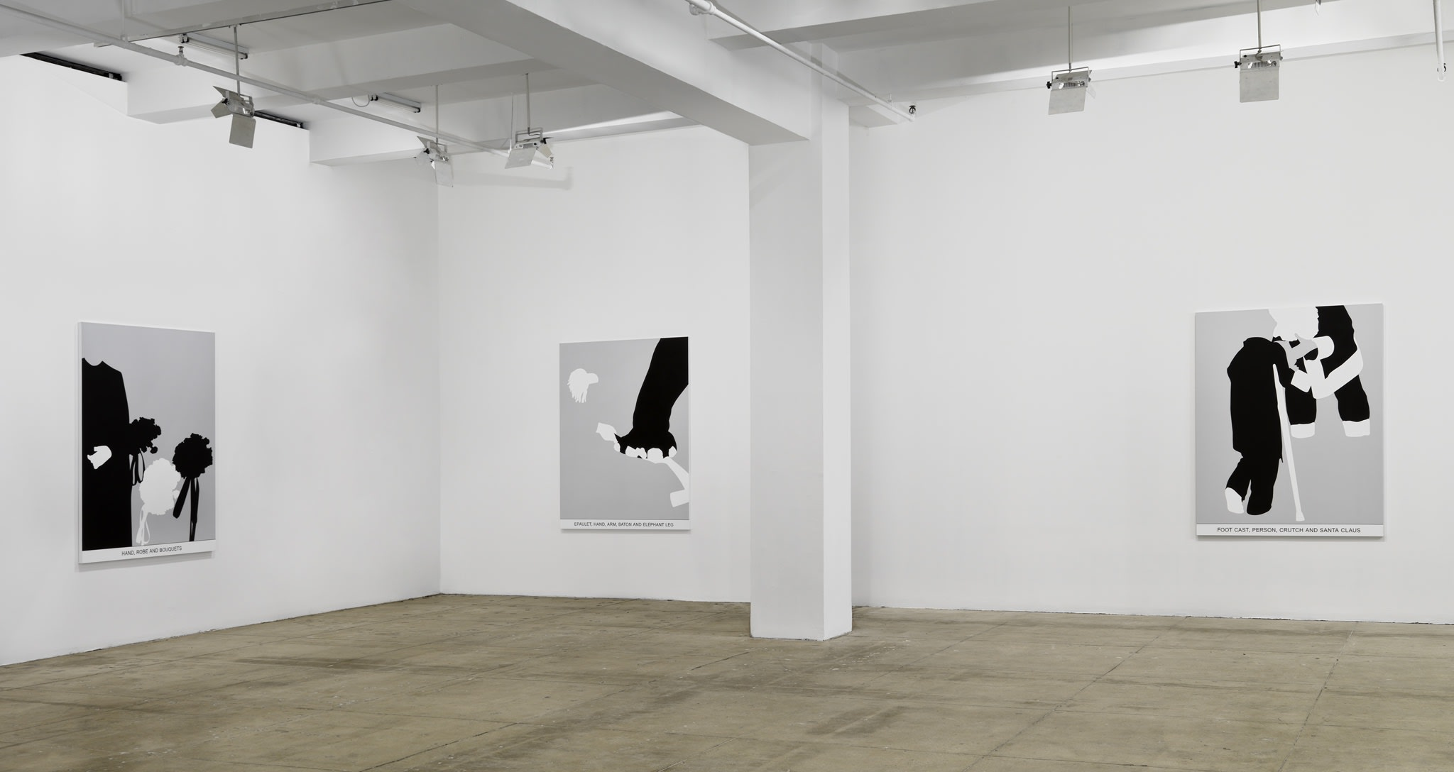 Three black and white paintings hang in a white space with a beige floor.