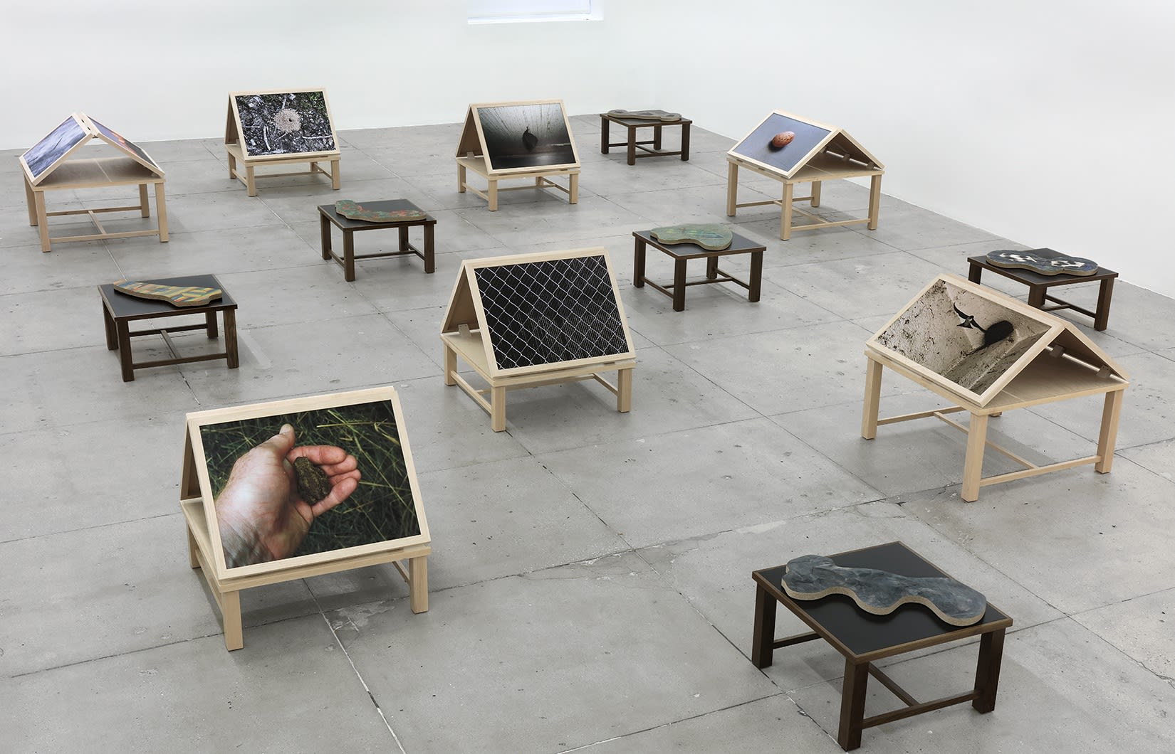 13 wooden platforms display color photographs and flat sculptures over a concrete floor.