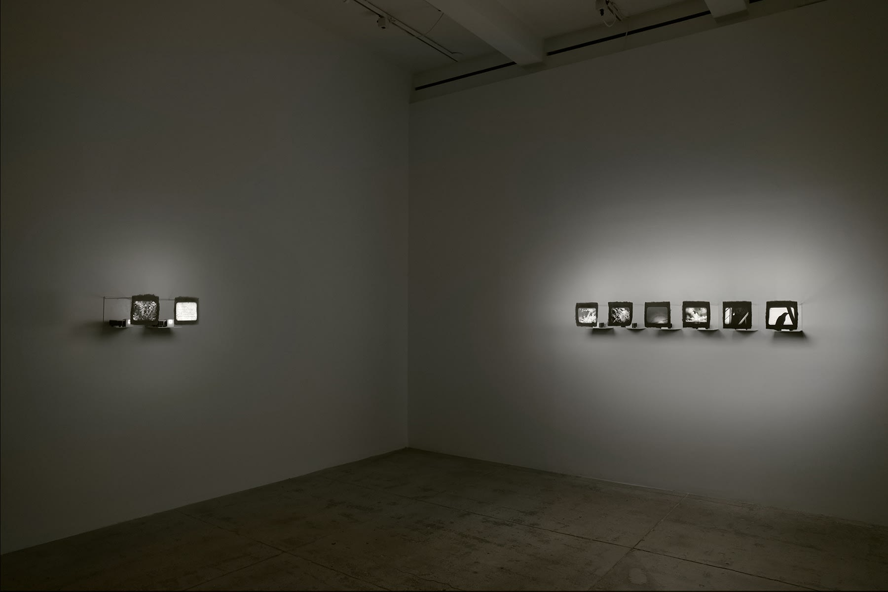 Eight small projected behind various fabrics and plates illuminate a dimly lit room.