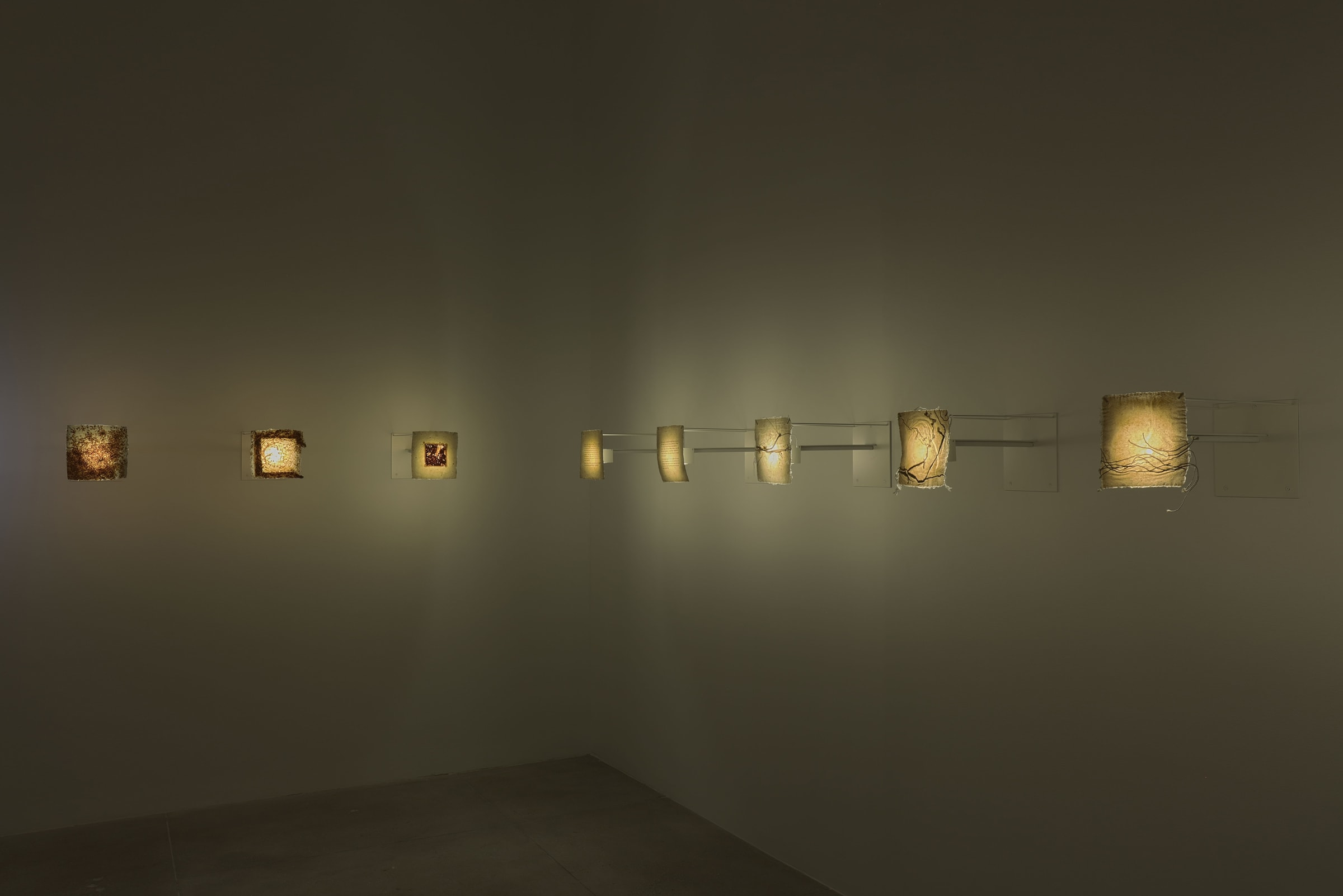 Eight small projectors behind various fabrics warmly illuminate a dimly lit room.