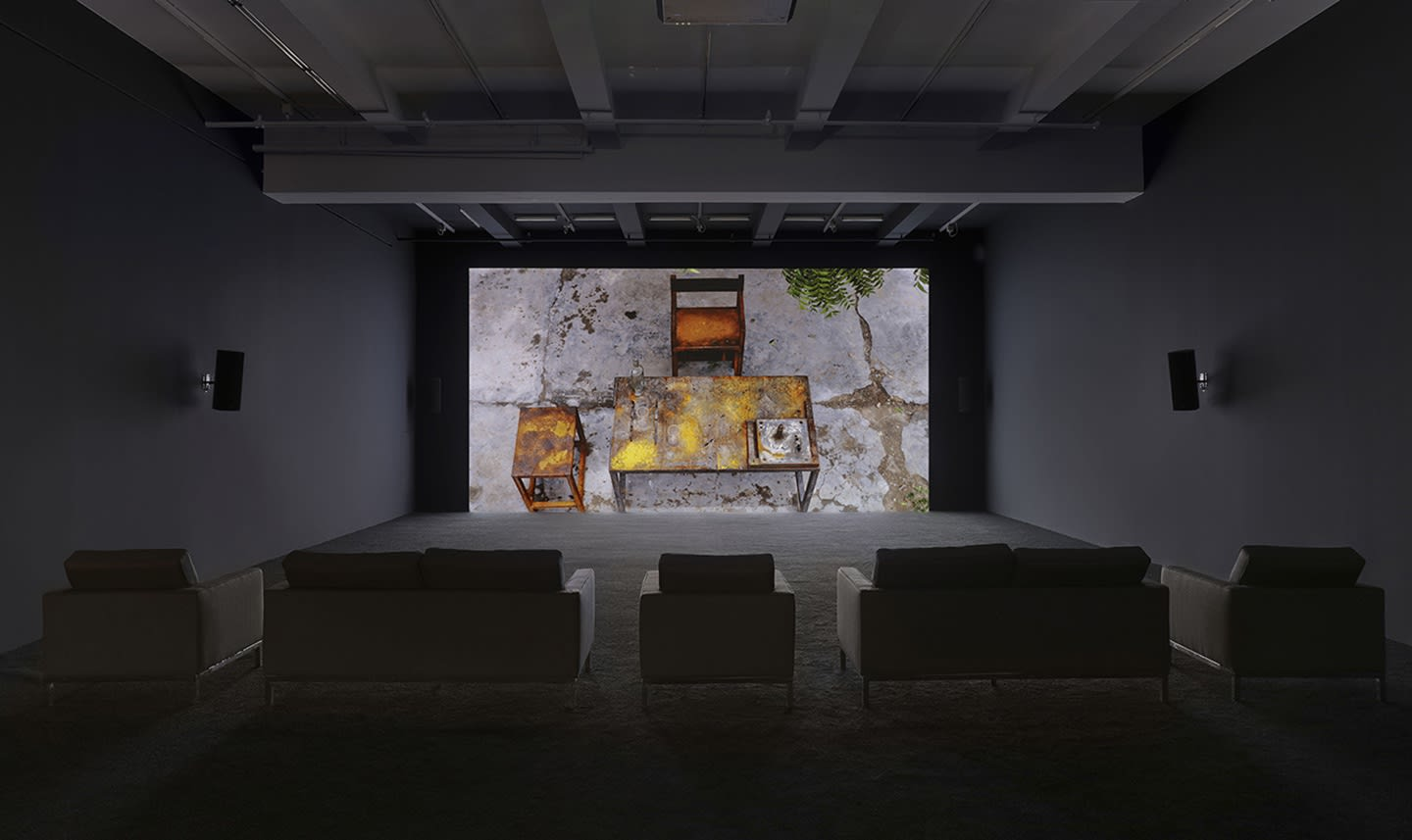 Various couches sit in front of a projection of a wooden table and chair in an outdoor setting.