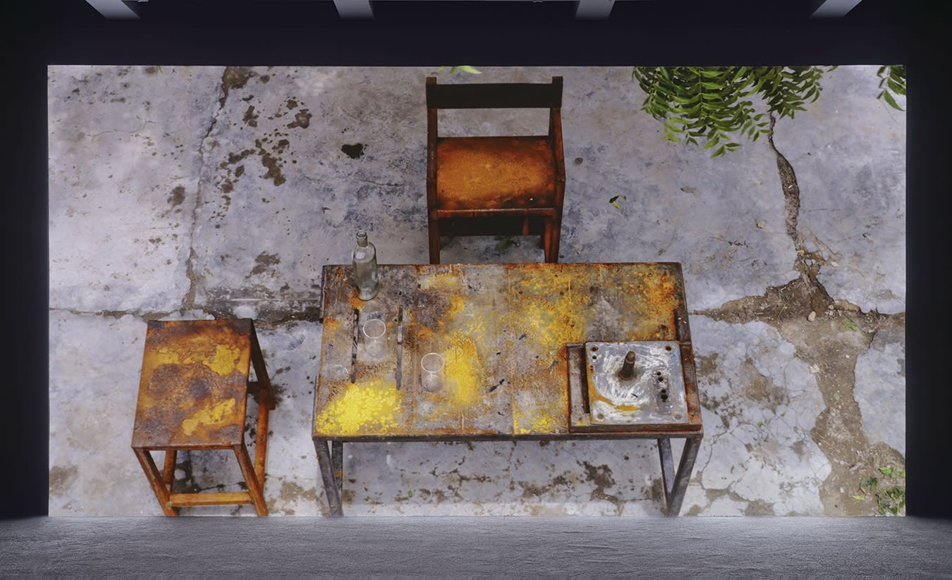 A large projection depicts a distressed wooden table and chair outdoors with two glasses and a bottle on top.
