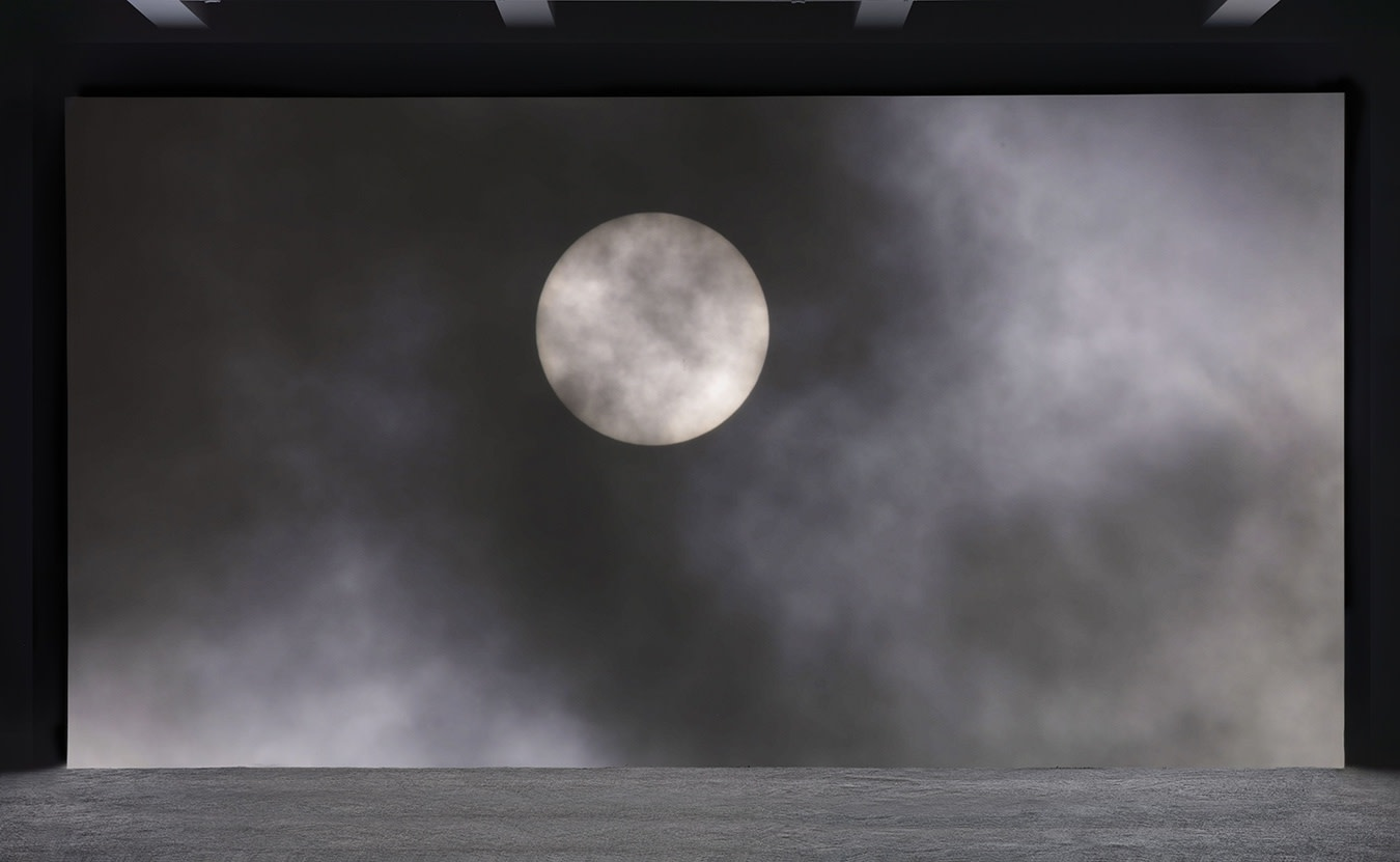 A large projection depicts a bright full moon behind translucent dark clouds.