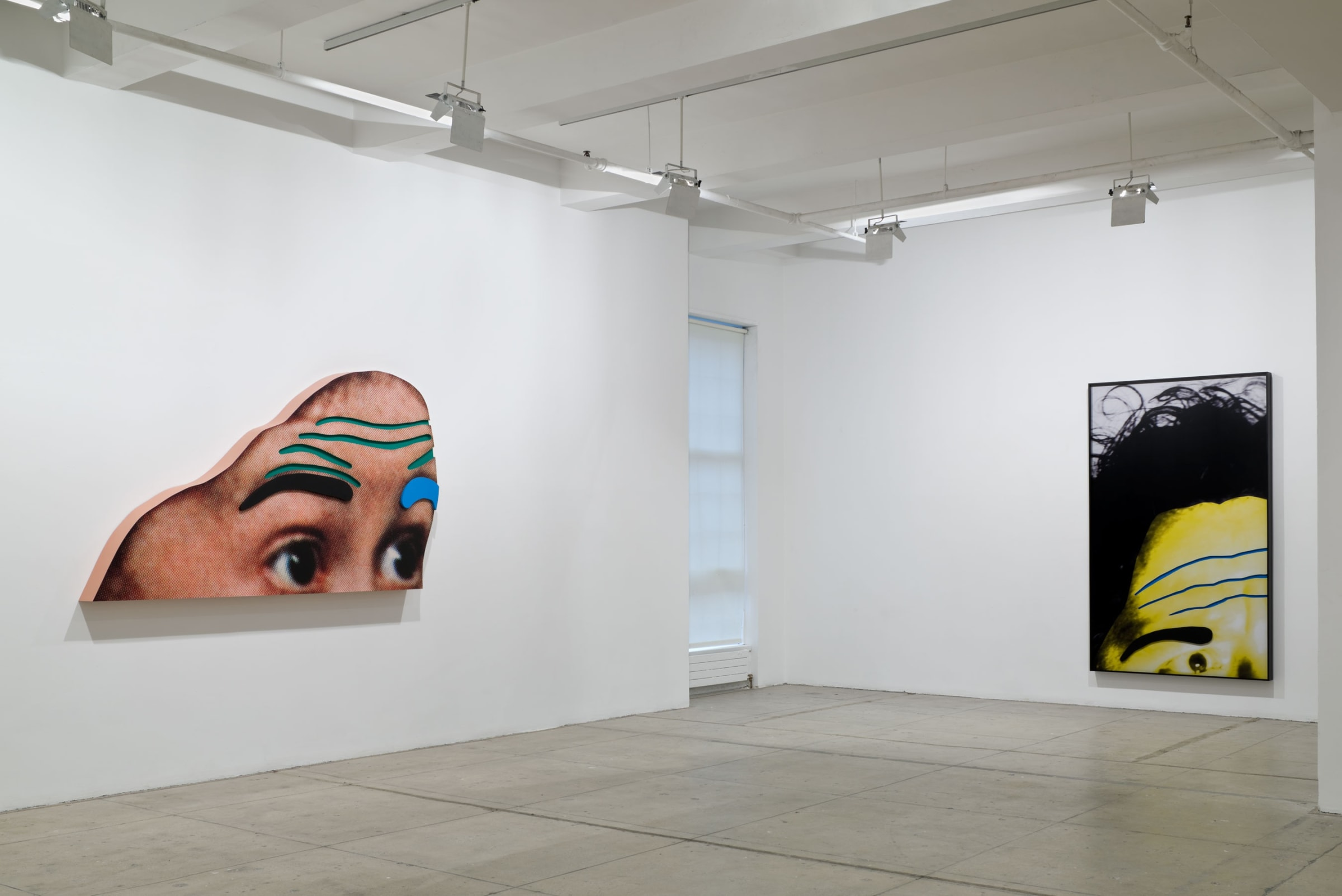 A large cut-out of eyes and a forehead on the left wall and a framed photograph of the top left half of a yellow face are marked with colors to exaggerate the foreheads and eyebrows.