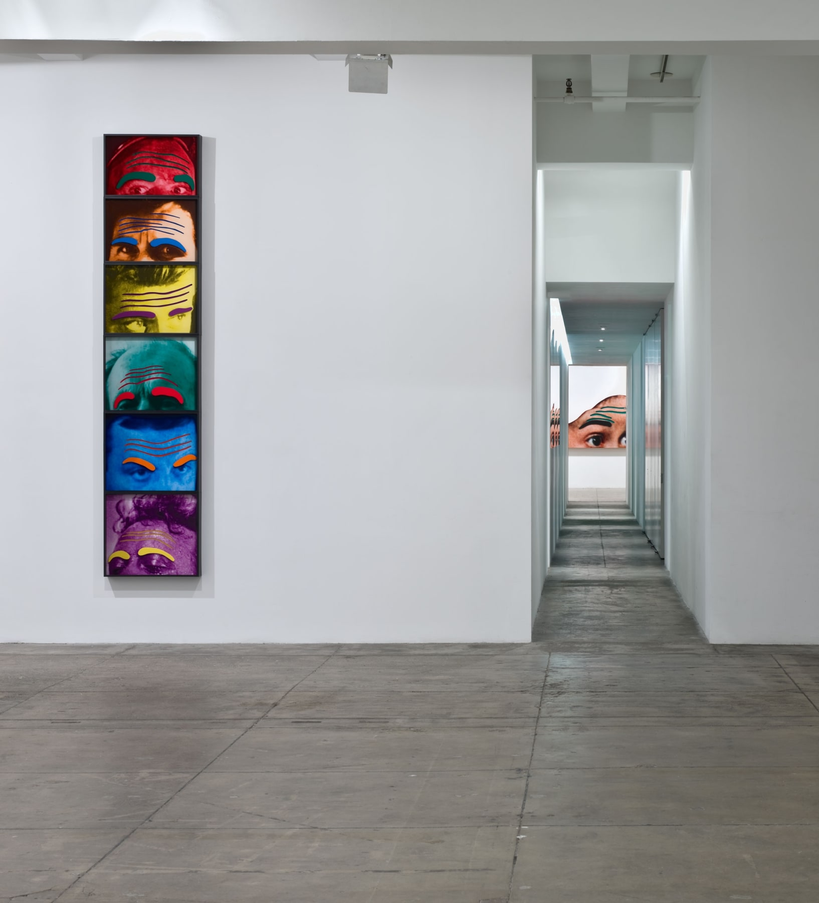 To the left of a long hallway, six framed images of foreheads in different colors are stacked on top of each other.