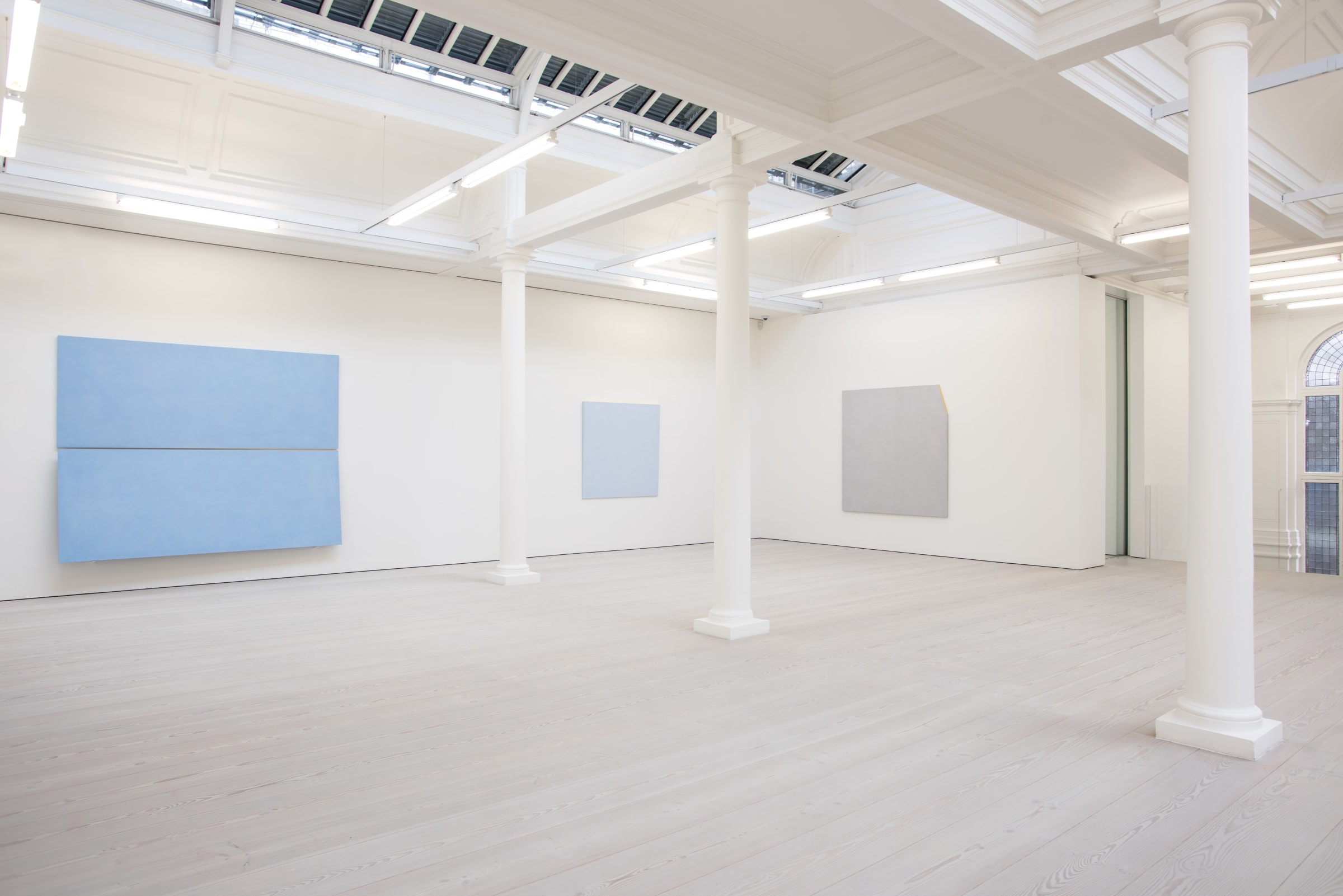 In a large white space with columns, two large light blue paintings hang, with one light grey painting.