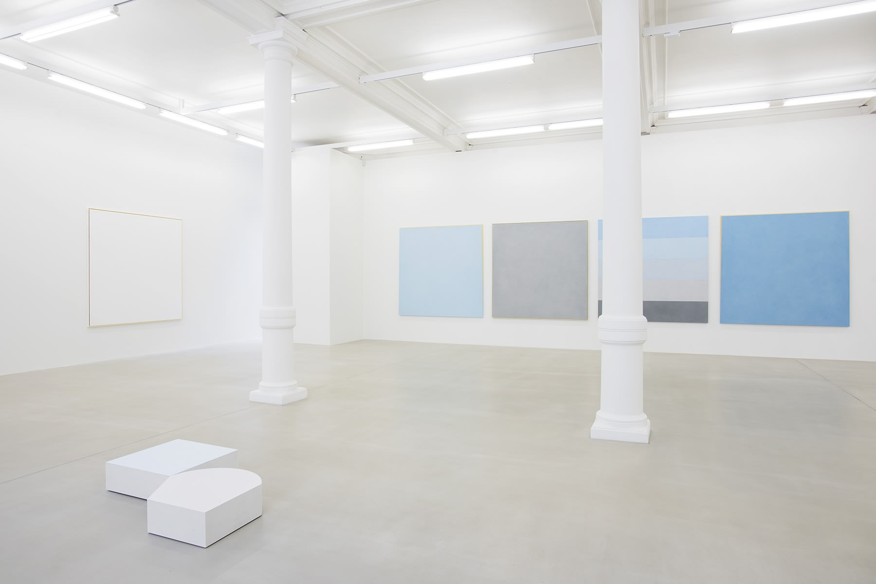 Various paintings of light shades (blue, grey, white) line the walls of an all white space, with short white sculptures on the floor.
