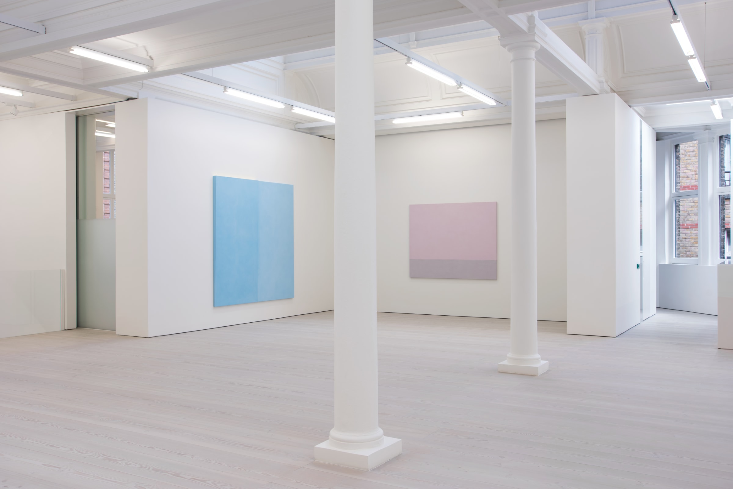 In a white gallery space with columns and a window to the left, two paintings hang: one light blue on the left wall, and one light pink straight ahead.