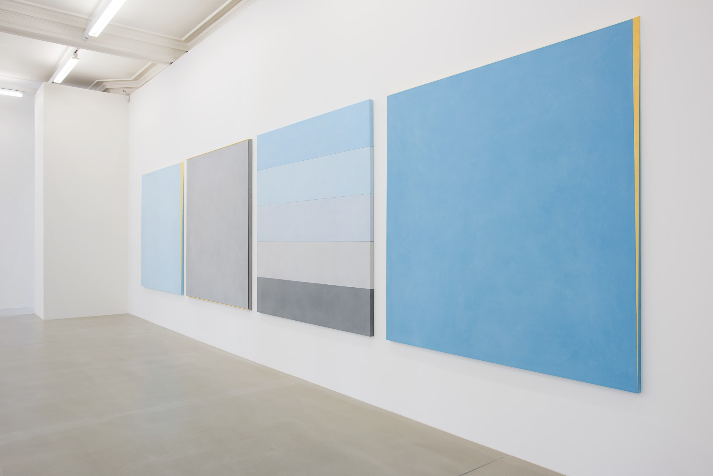 Four paintings hang on a white wall. From the left: solid light blue with gold framing, solid light gray with gold framing, 5 strips: light blue, lighter blue, light grey, grey,  darker grey, and finally, sky blue with gold framing.