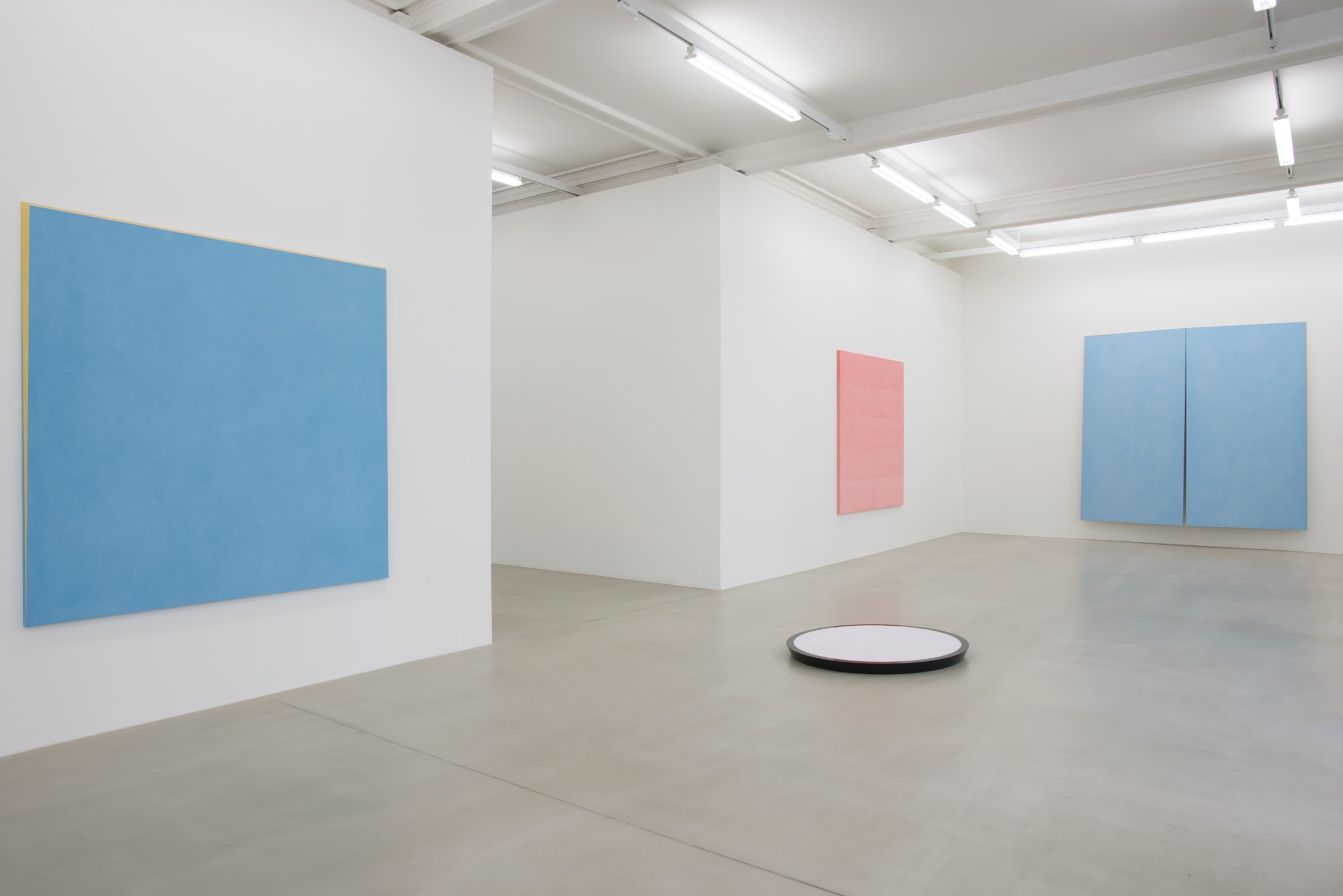 In a large white space with grey stone floors, a white circular sculpture with black trimming lies on the floor. On the walls surrounding it hang a light blue painting with gold trim, a light pink painting, and a larger blue painting, bisected.