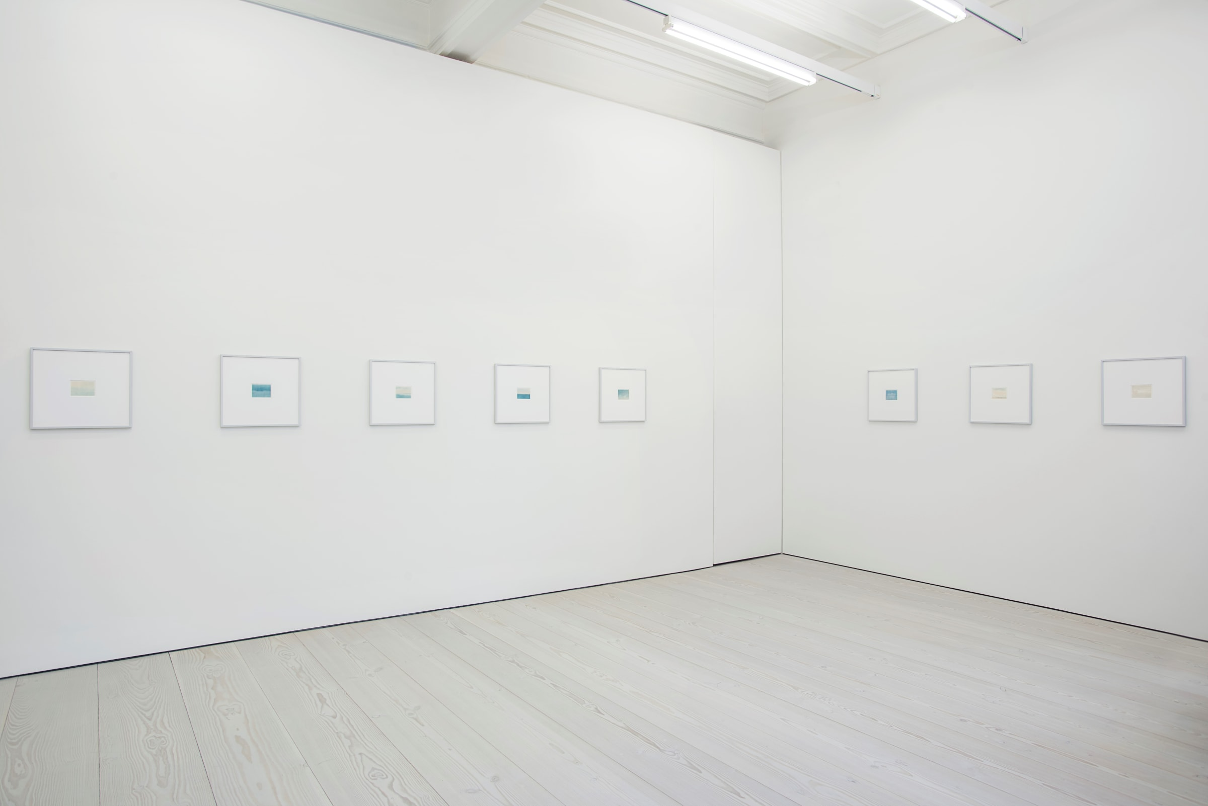 In a white space, 8 small drawings, 5 on the left wall and 3 on the right, hang. They are framed in white, and mostly made up of blues and yellows, like sunsets.