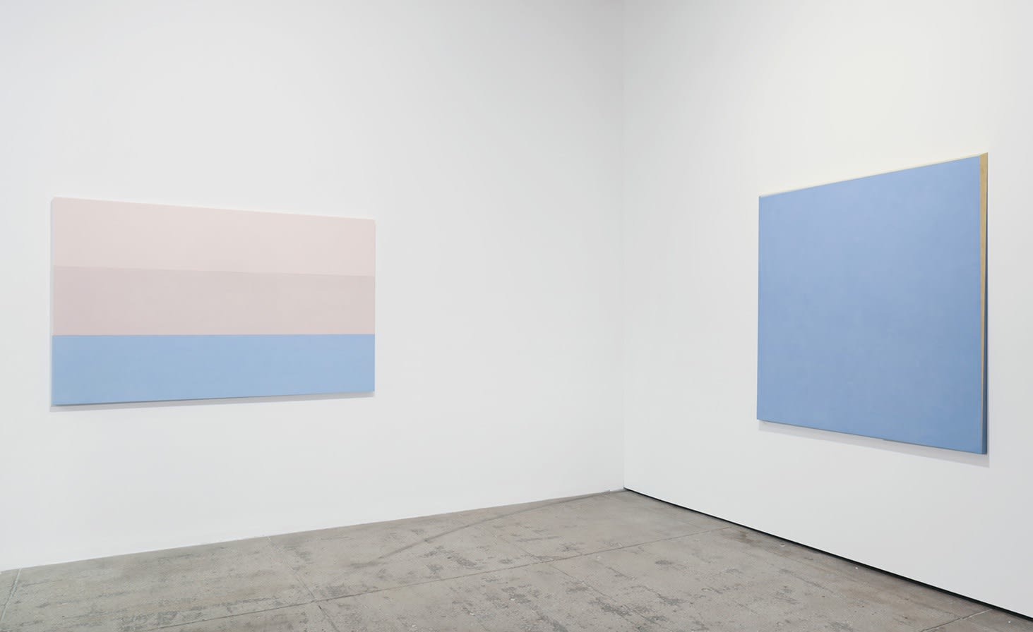 2 pastel colored paintings in pink and blue hang in the corner of a white room.