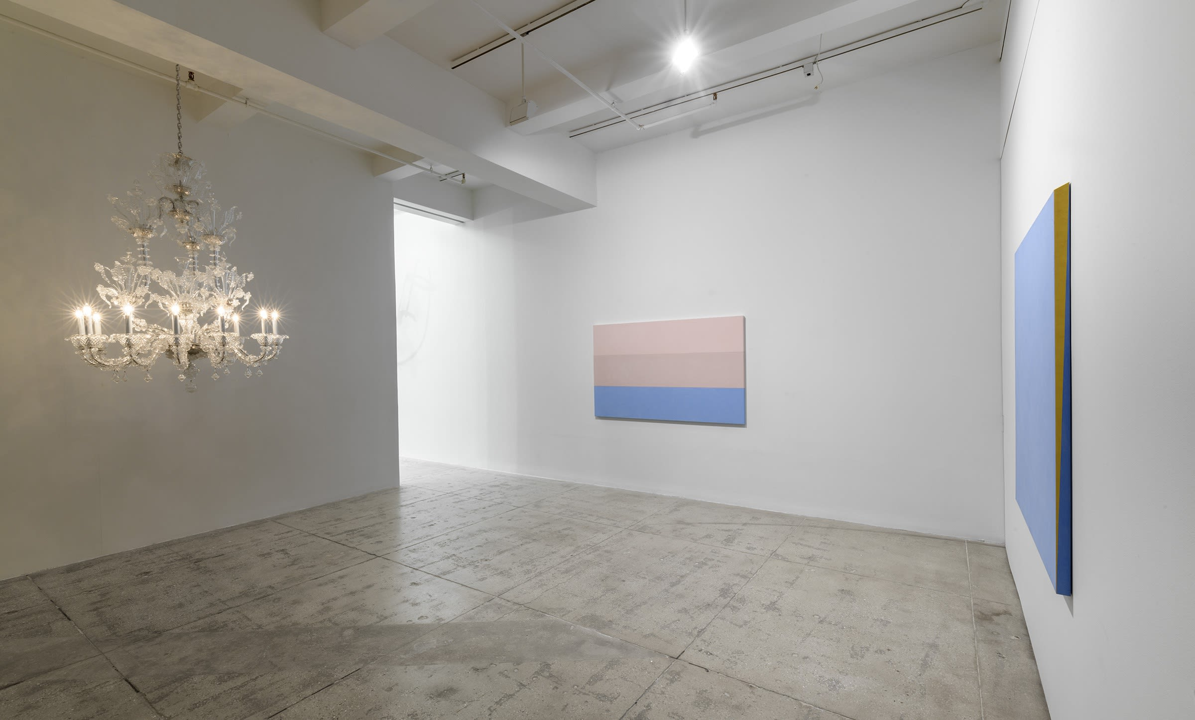 2 blue and pink paintings hang in the gallery; there is a chandelier hanging from the ceiling to the left.
