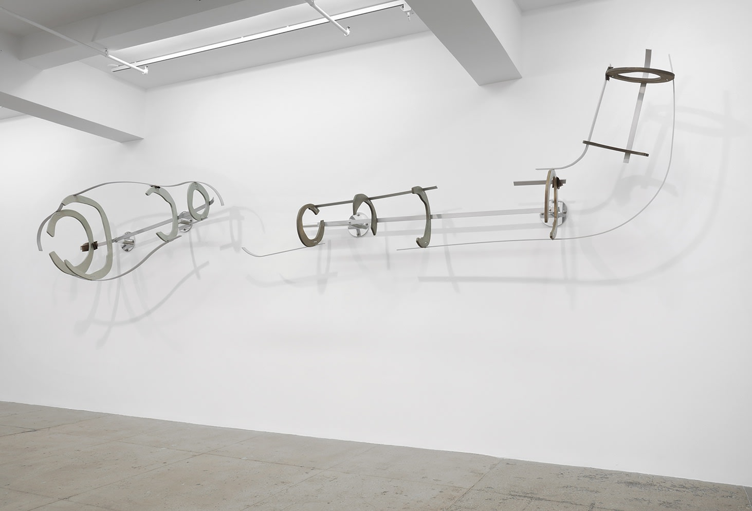 An abstract sculpture is attached to the wall in various pieces connected by thin metal wire.
