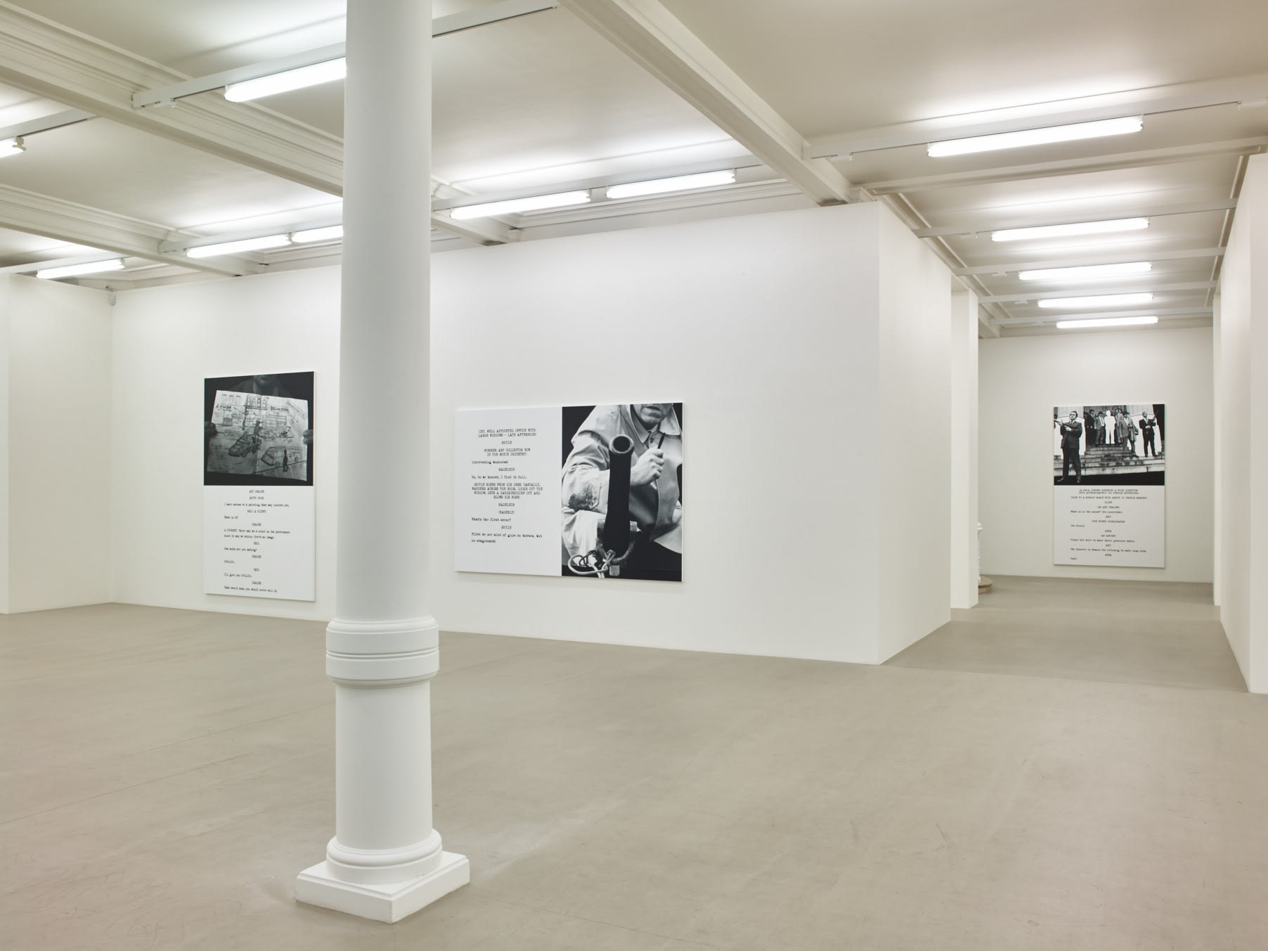 In a large white space with columns, 3 large paintings hang. Each are roughly half image and half text, which is in the format of a film script.