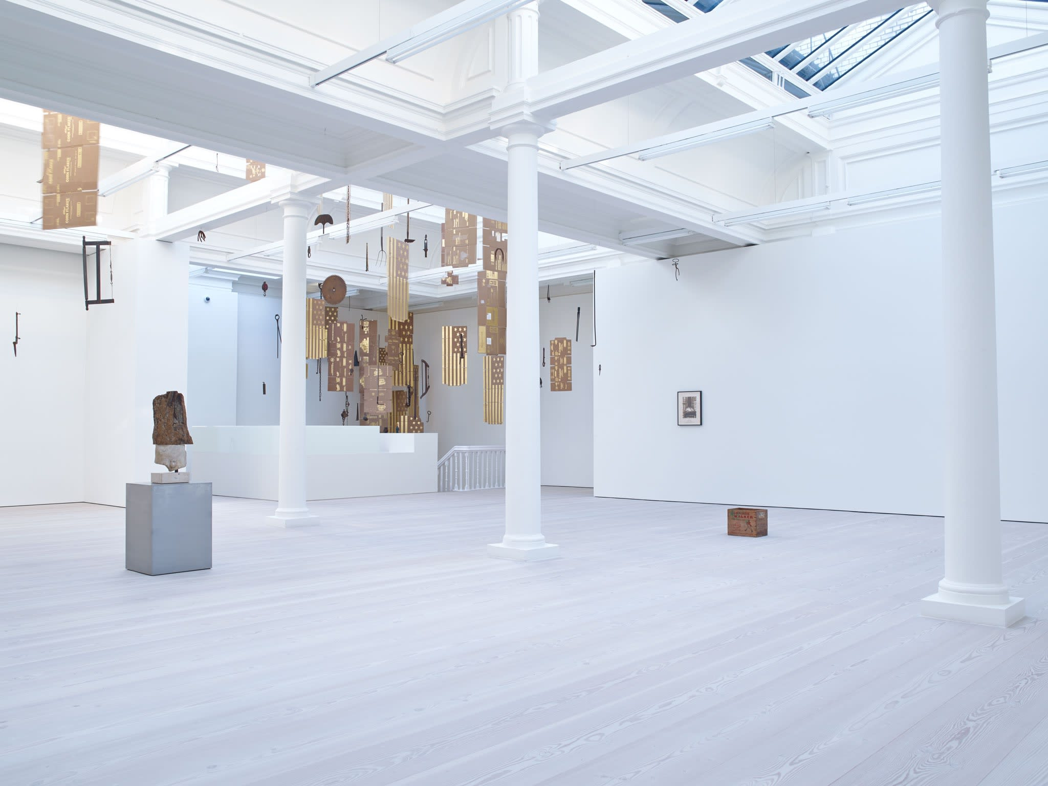 In a large white space with a long glass skylight, sculptures hang from the ceiling - most seem to be American flags, with 13 stars, made out of gold painted cardboard.