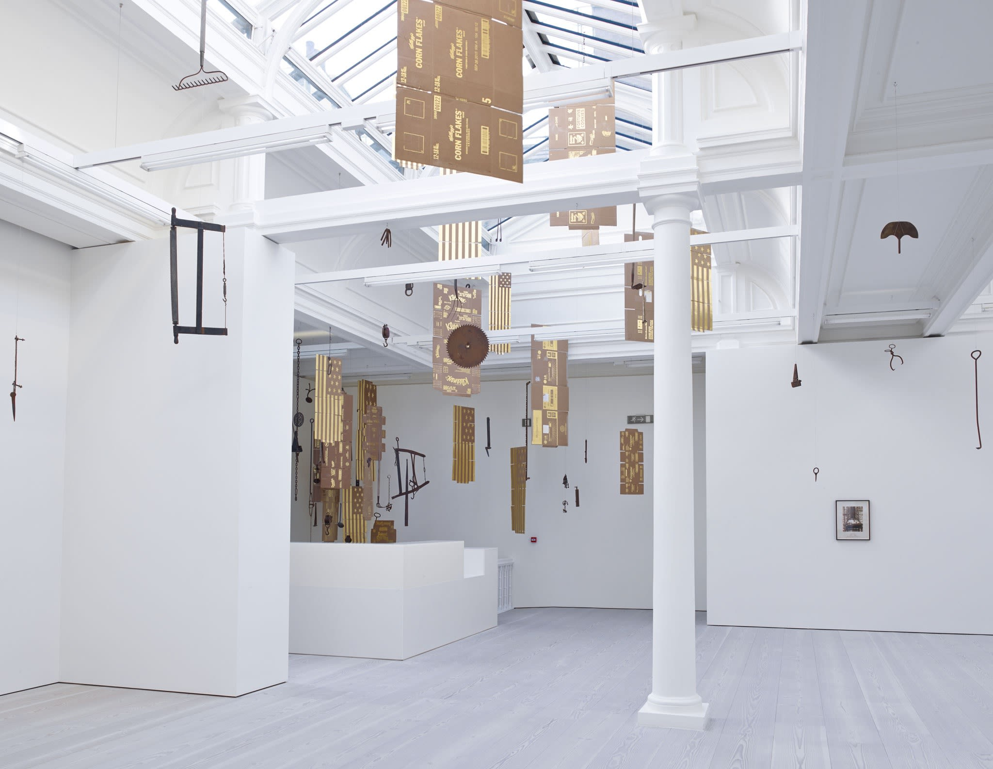 In a large white space with a long glass skylight, sculptures hang from the ceiling - most seem to be American flags, with 13 stars, made out of gold painted cardboard. Another is an unfolded Corn Flakes box, made from the same material.
