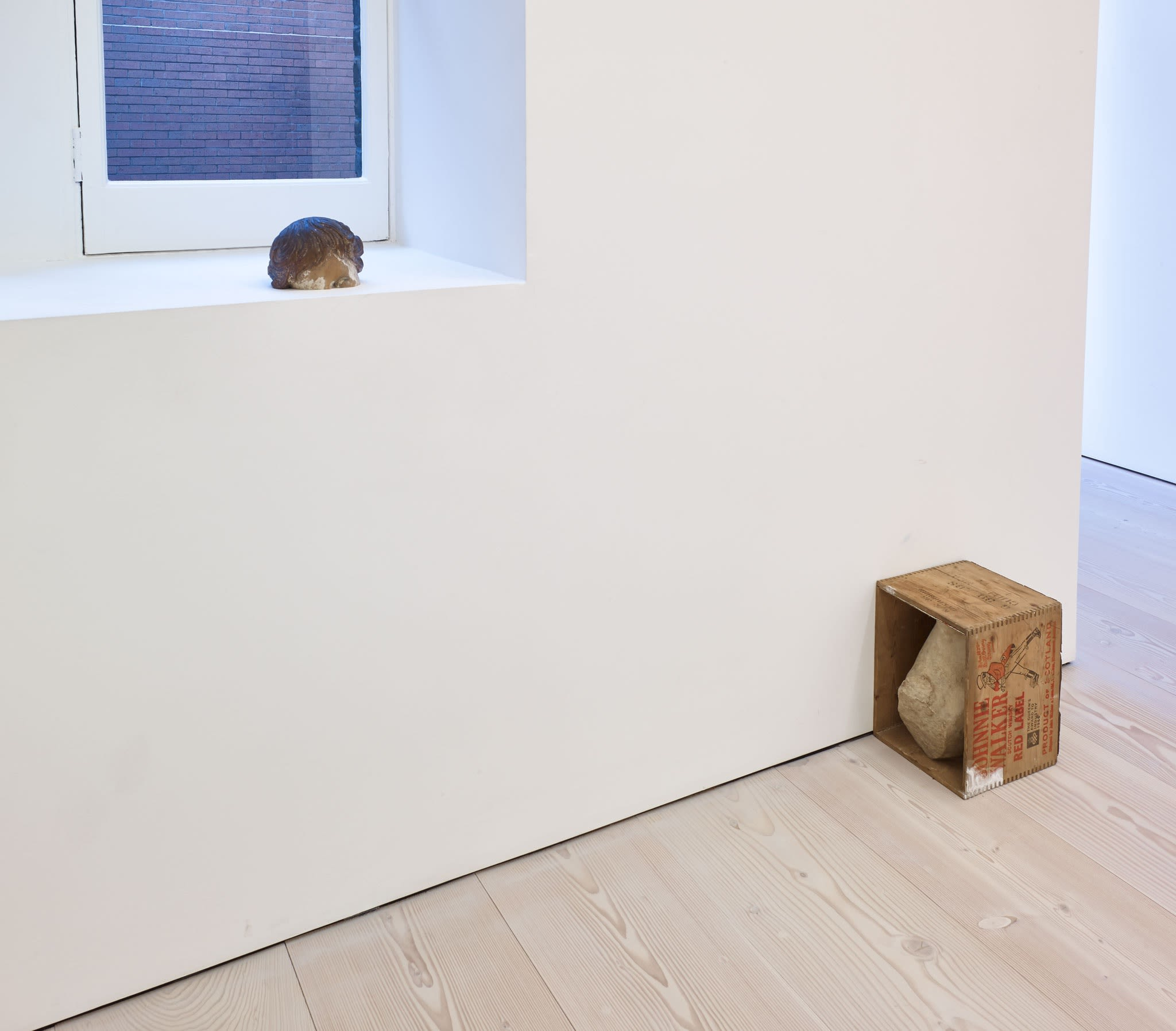 A small, unidentified object sits on a deep, white windowsill. On the white wooden floor, another sculpture sits: a large rock, stuck inside a sideways wooden box, which reads JOHNNIE WALKER RED LABEL.