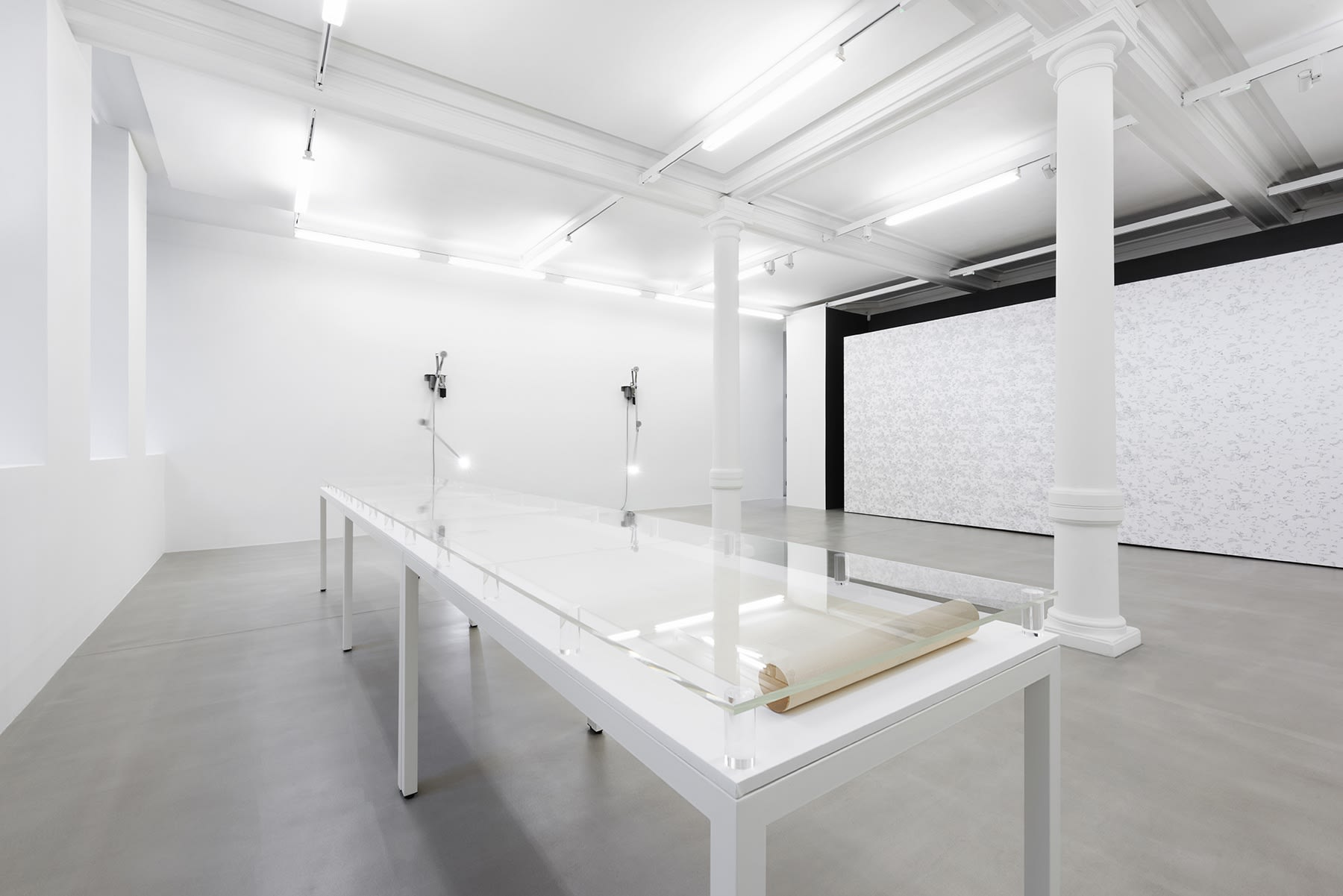 2 lights point to a long white display table in a white gallery space with columns.