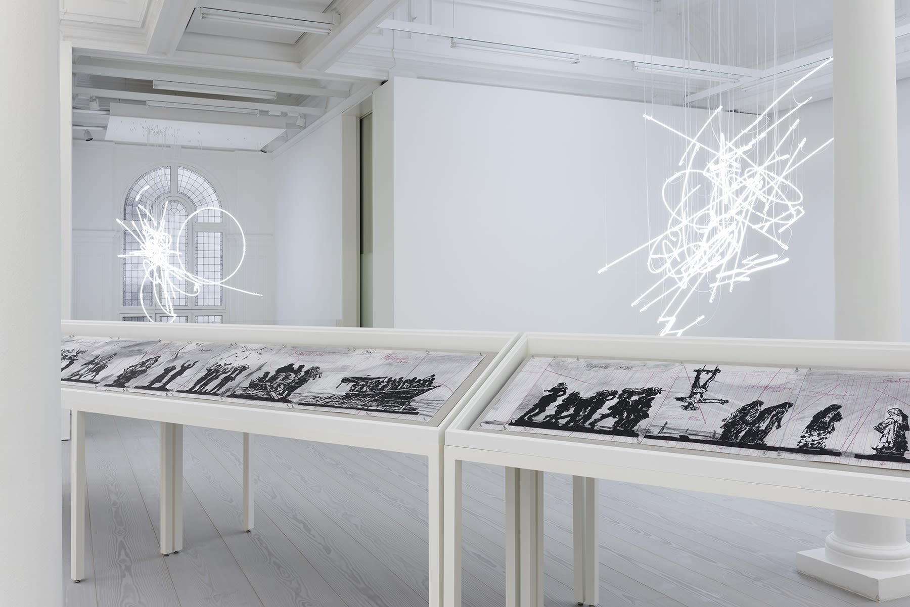 A long vitrine displaying charcoal drawings sits under a neon sculpture hanging from the ceiling.