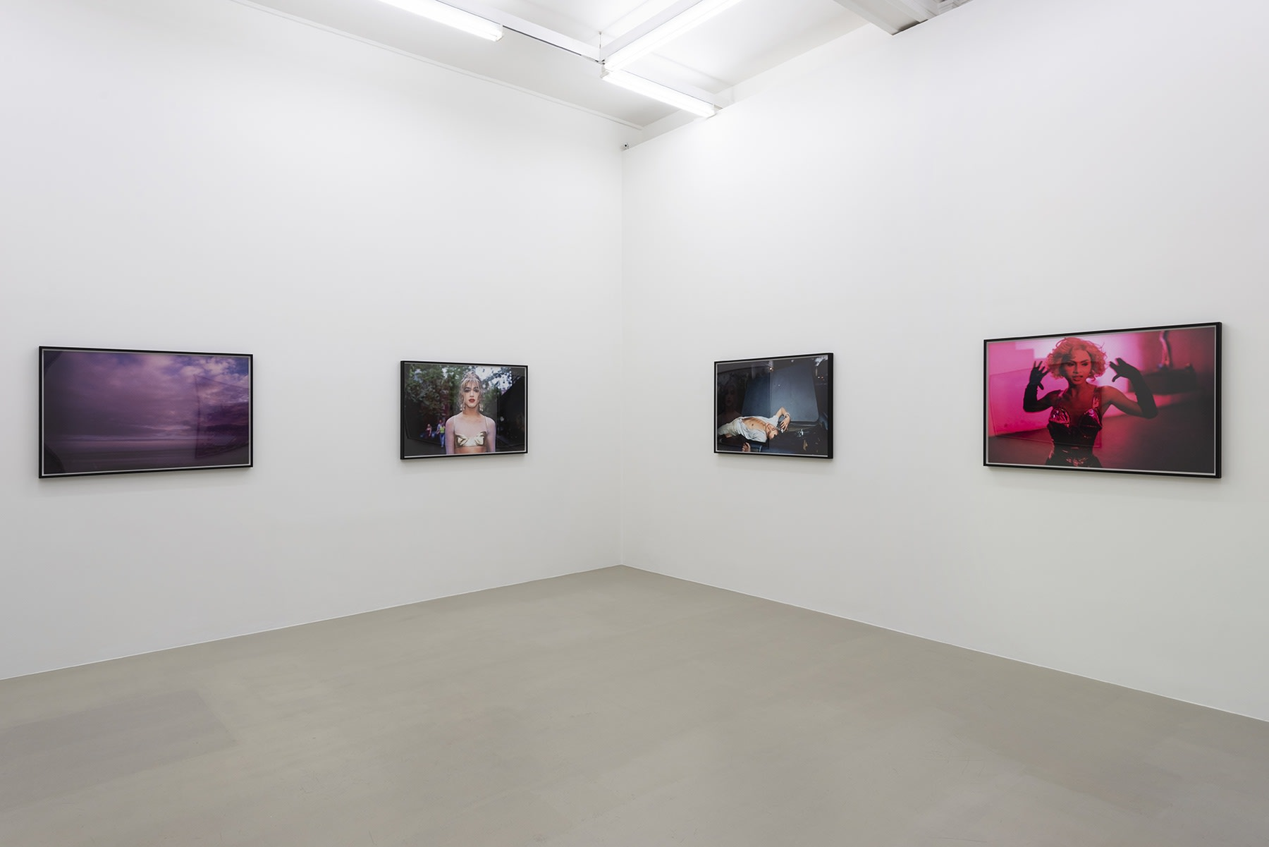 4 colorful photographs hang in a white gallery space.