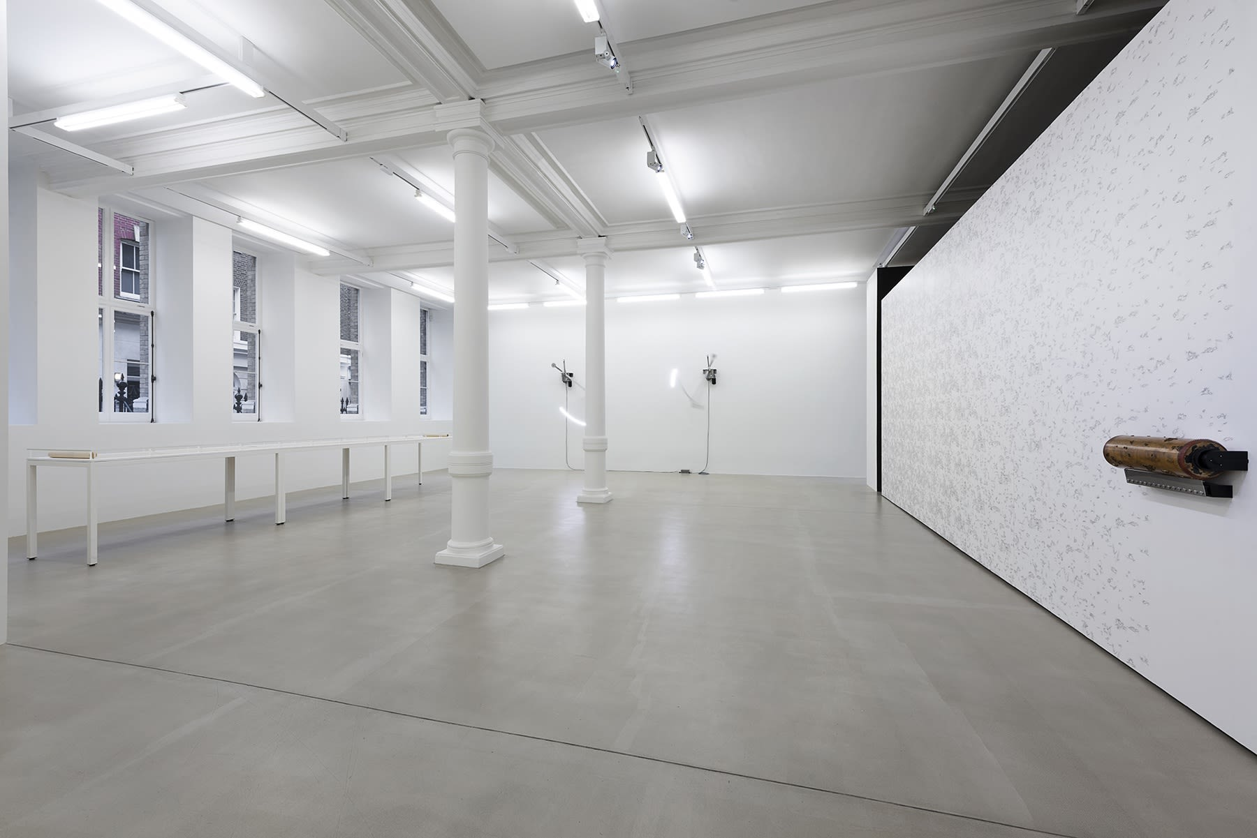 A white gallery room; the wall on the right has a pattern that has been inked on with a roller.