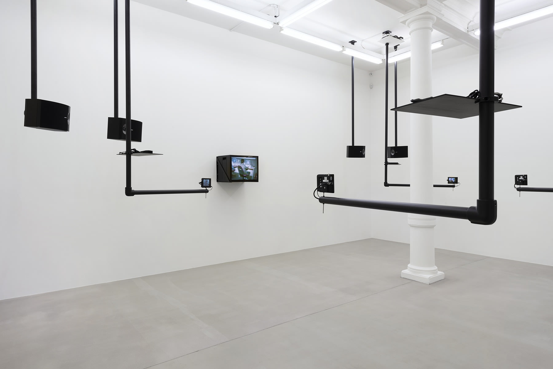 Black pipes attached to the ceiling at right angles hold various sized monitors.