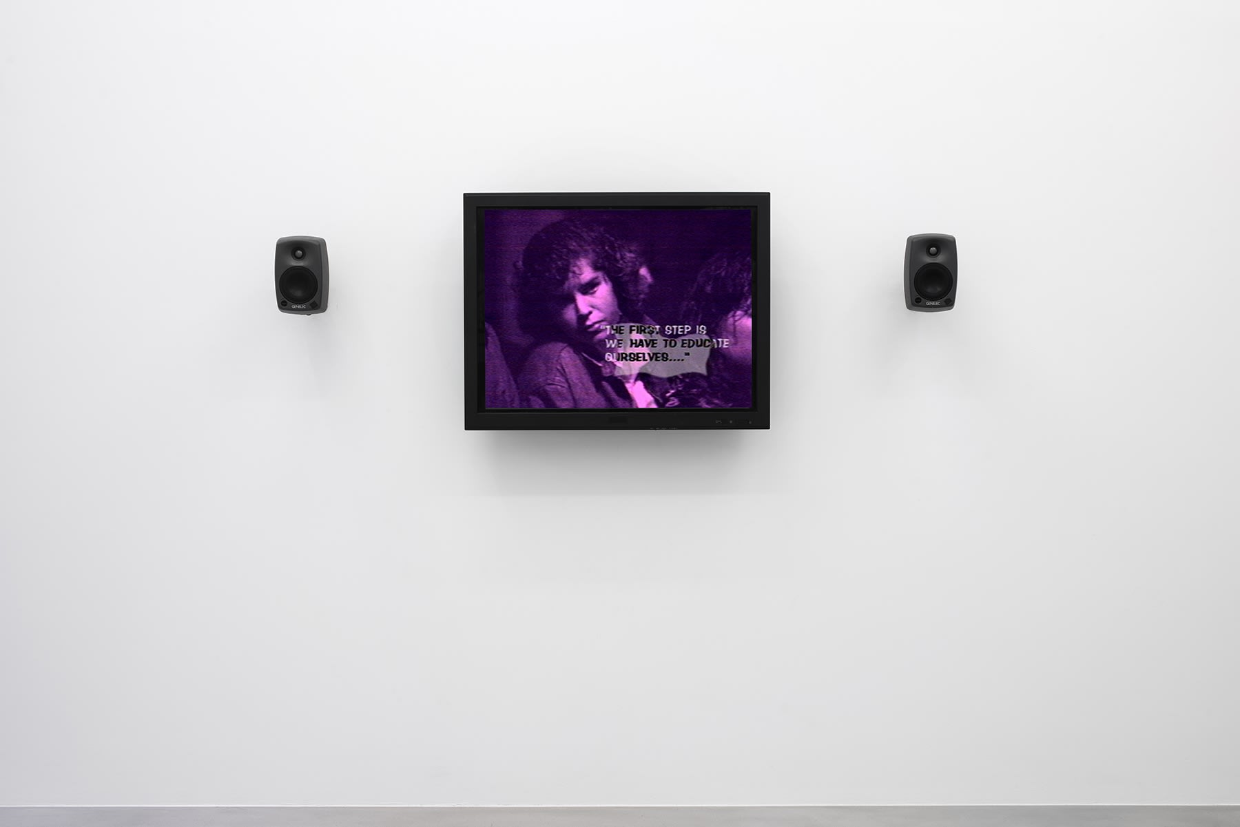 """A purple monitor with 2 speakers displays a woman with text reading """"The first step is we have to educate ourselves."""""""