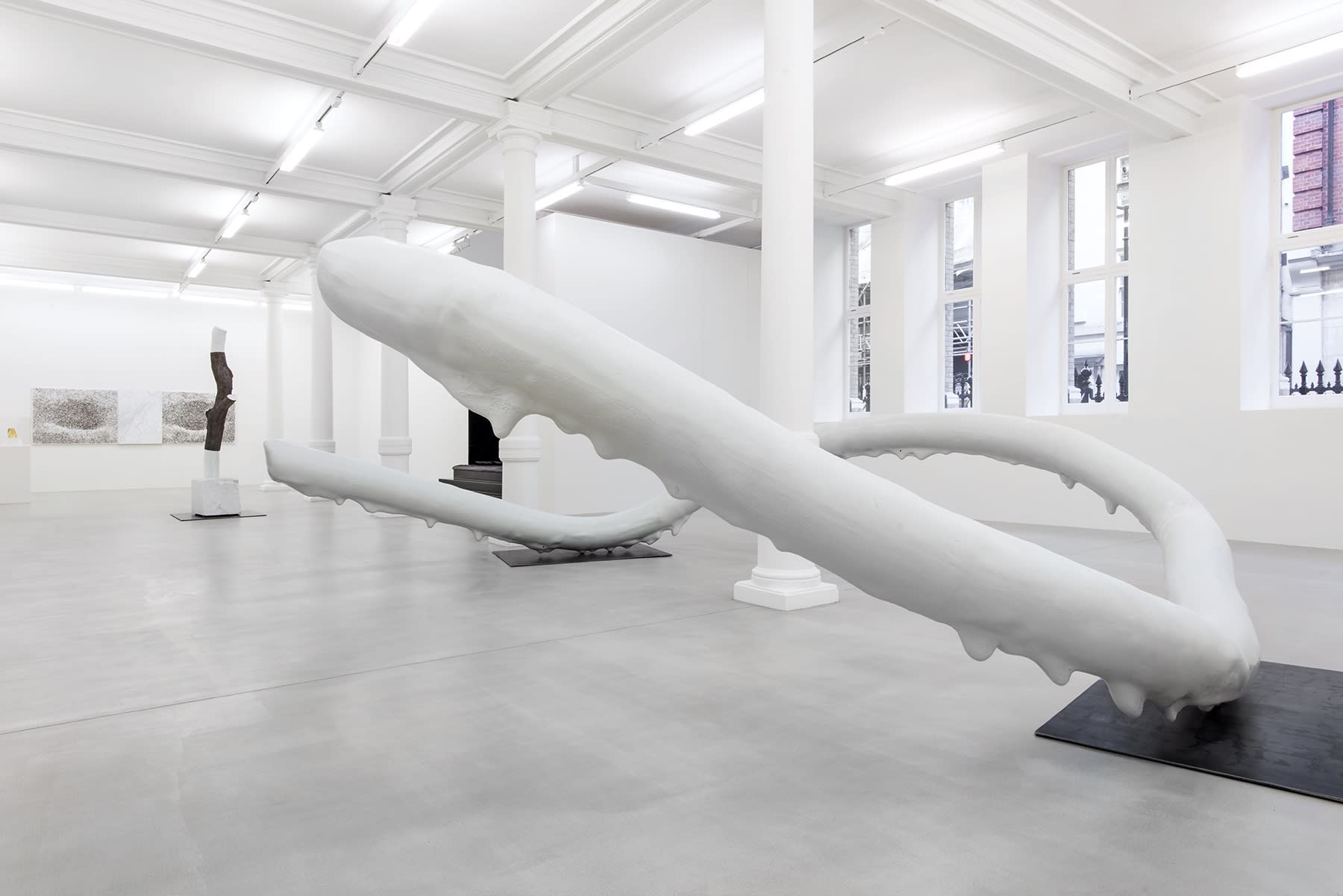 An abstract sculpture that appears to be dripping with white paint sits among other artworks in a gallery.