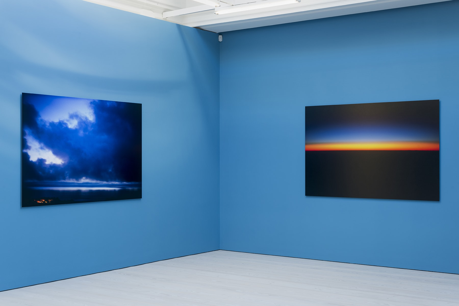 2 large color photographs of horizon lines at sunset hanging on a bright blue wall.