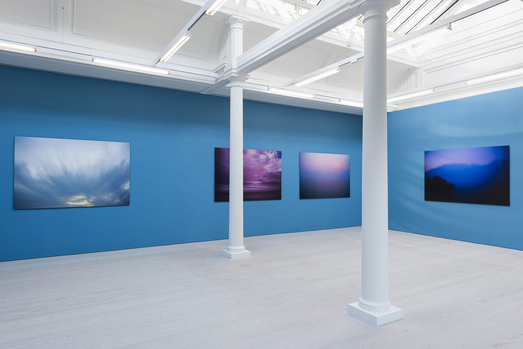 4 large color photographs of the sky hanging on a bright blue wall in a room with skylights and 2 columns.