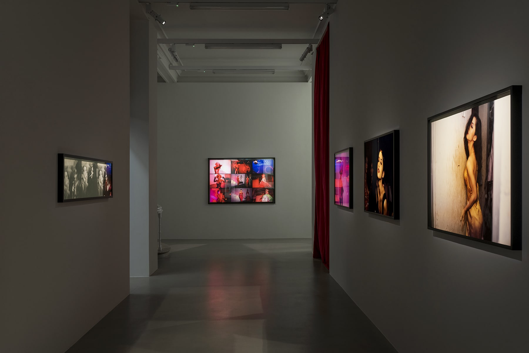 5 spotlit framed photographs on a grey wall with a red curtain leading to another room on the right.