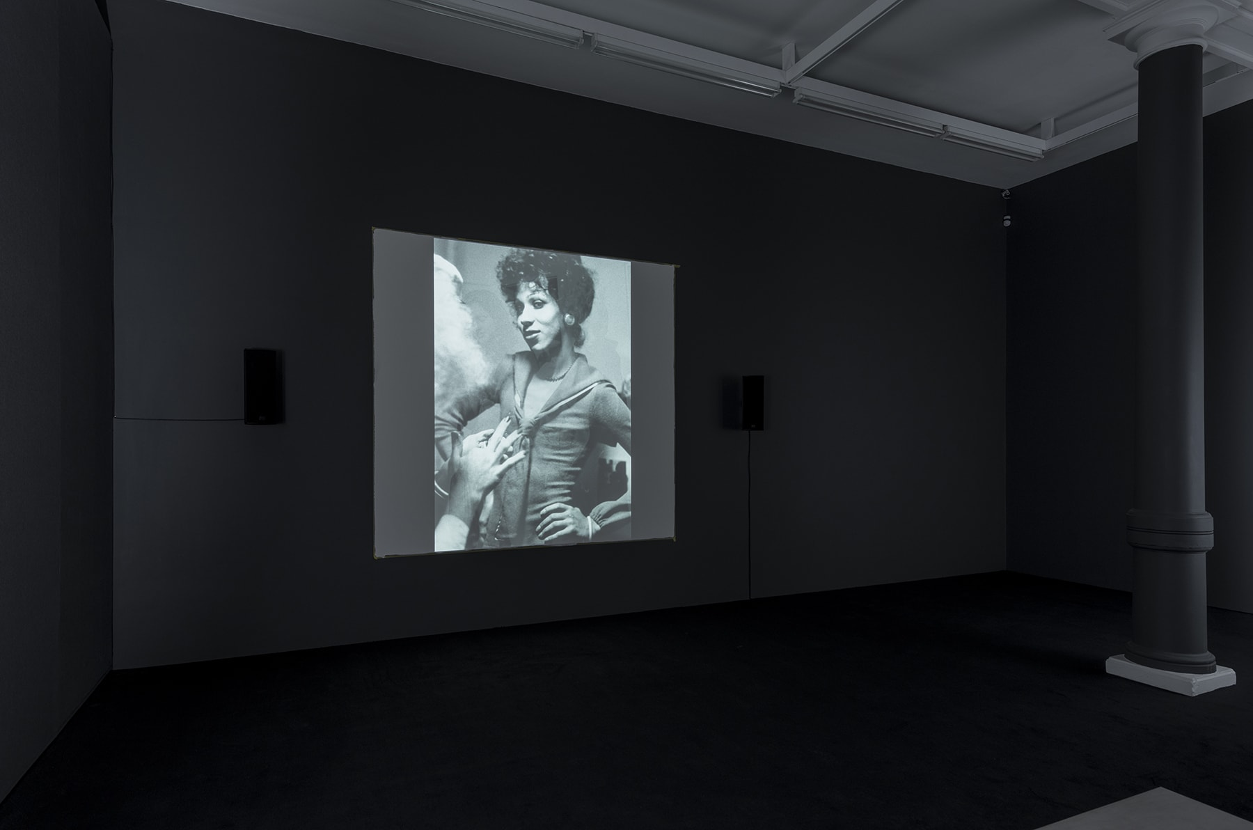 A black and white projection of 2 people talking, one with their back to the screen and the other with hands on their hips.