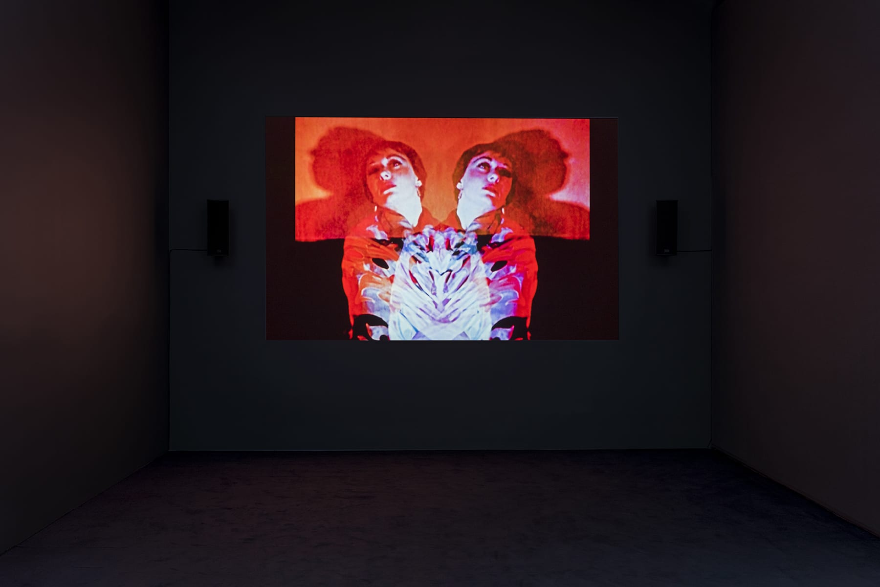 A red projection in a darkened room of a double image of a woman.