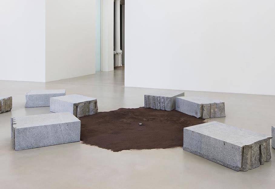 Installation of carved stone blocks around brown suede rug.