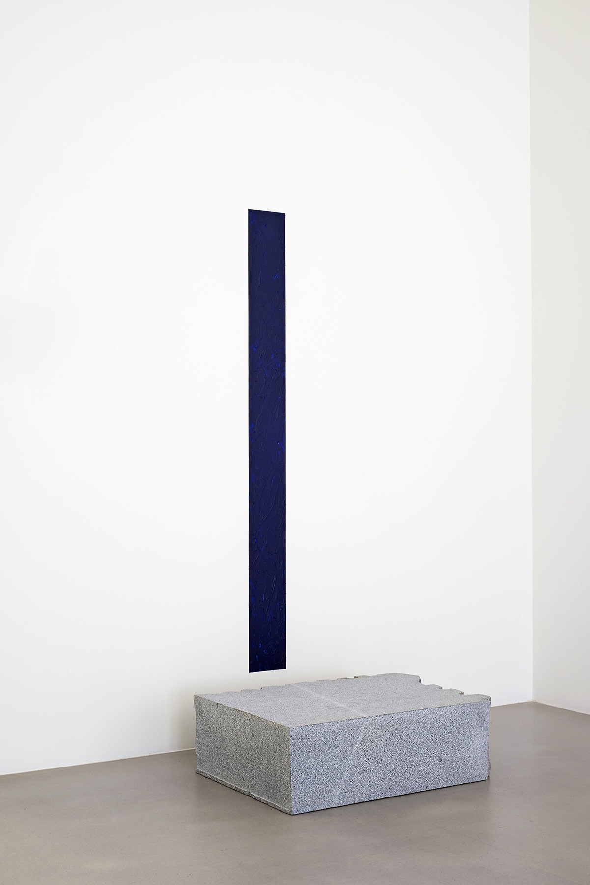 Skinny deep blue painting mounted above slab of granite.