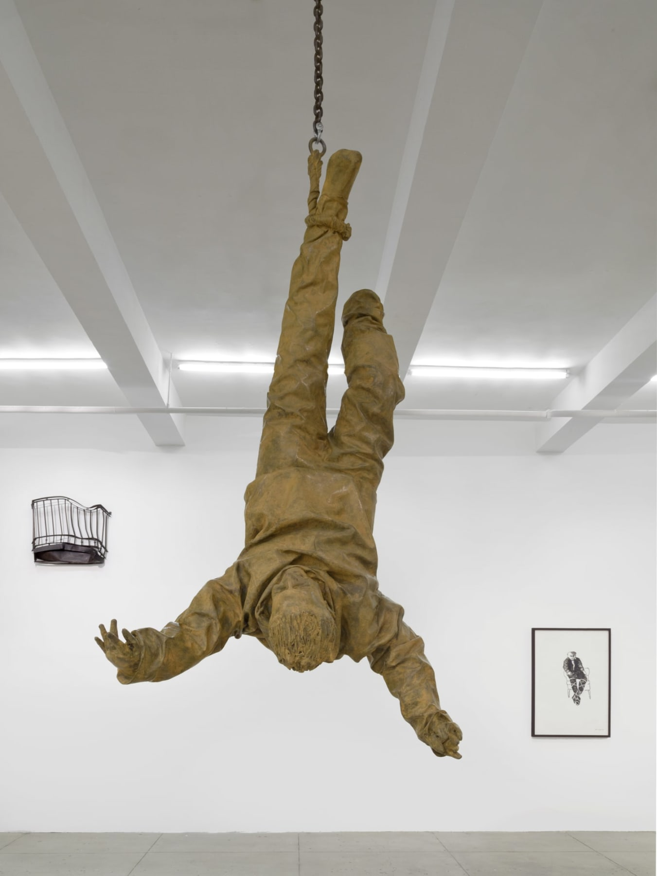 Sculpture of person suspended in air upside down by the foot