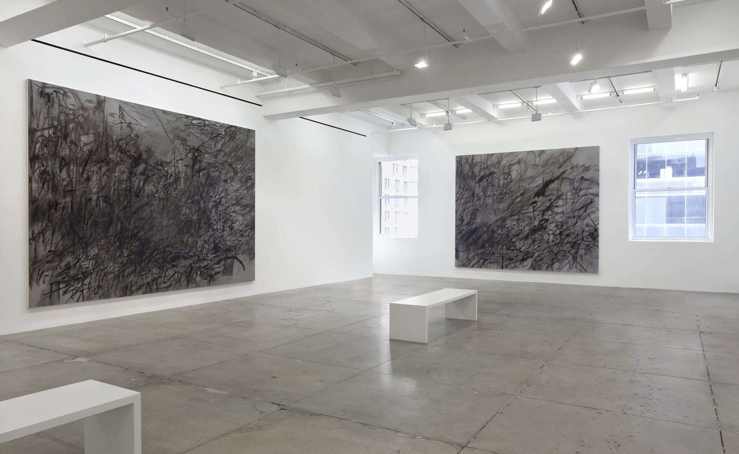 2 abstract paintings hang in a white gallery space with a bench.