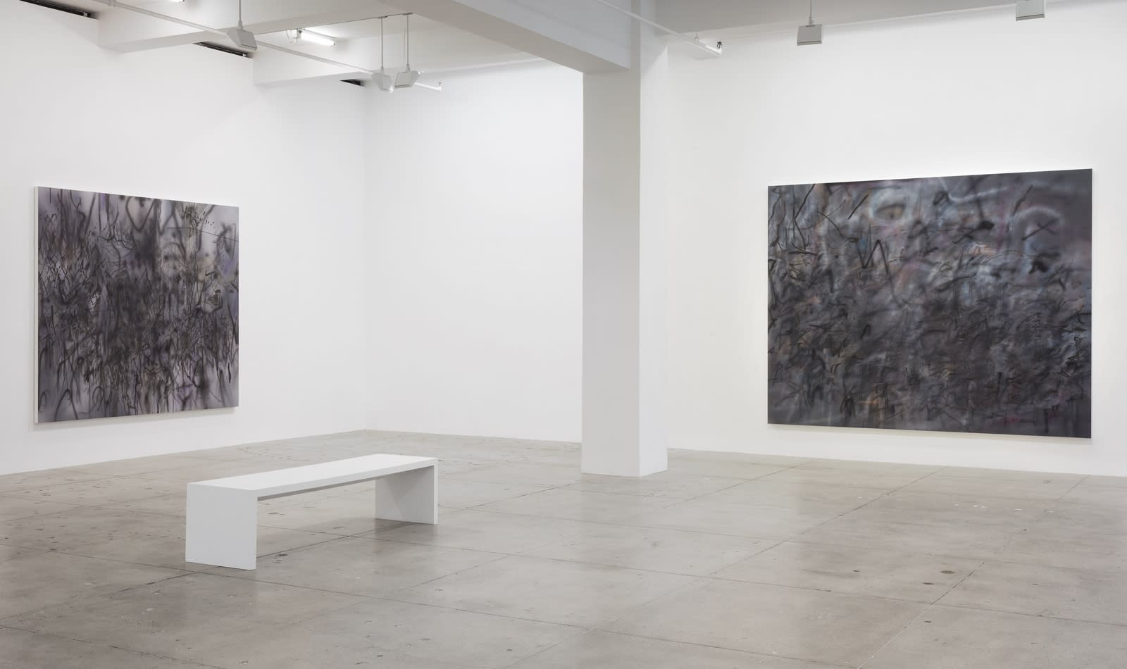 2 abstract paintings hang in a white gallery space with a white bench.