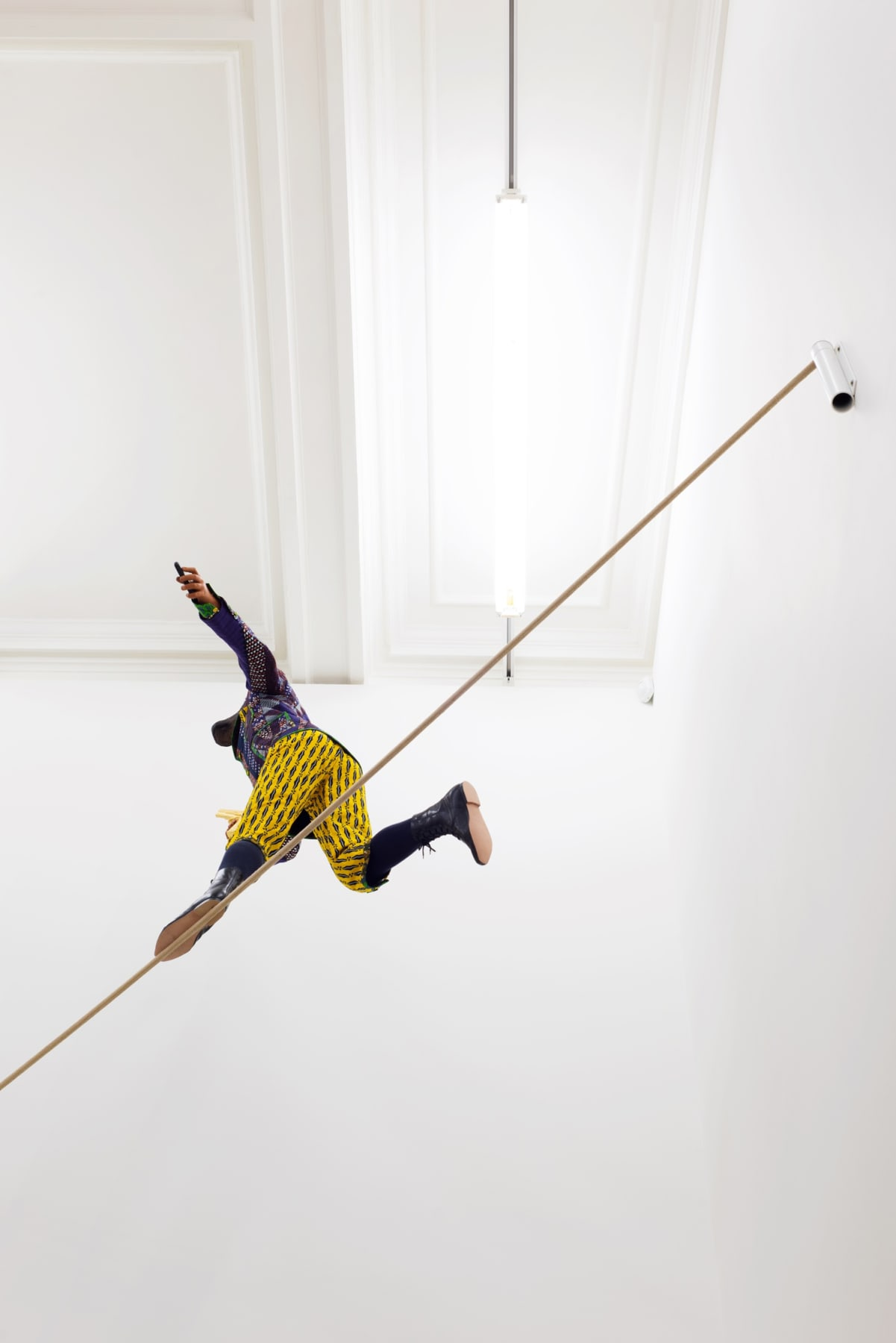 Installation view from underneath of miniature figure with a cow head and human body in wildly colored garments on a tightrope clutching a gun.