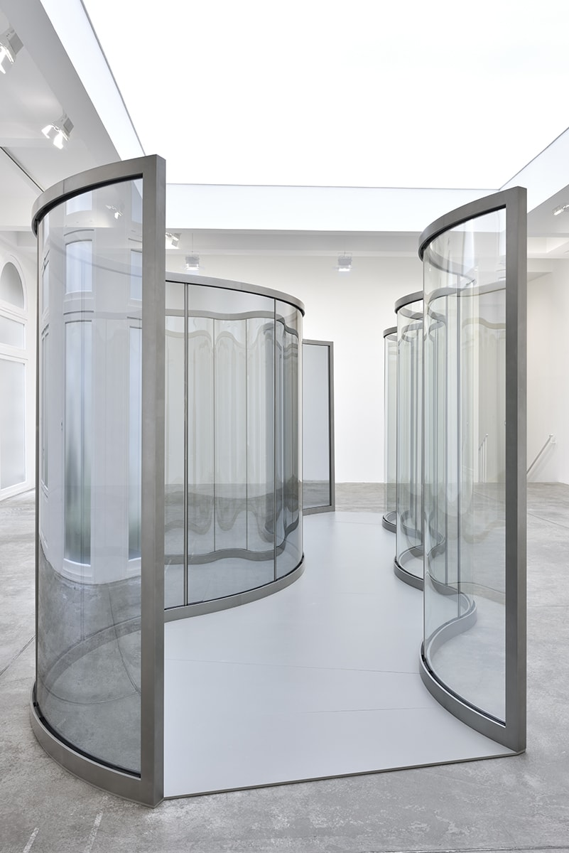 2 wavy panes of glass create a corridor in the center of a bright room.