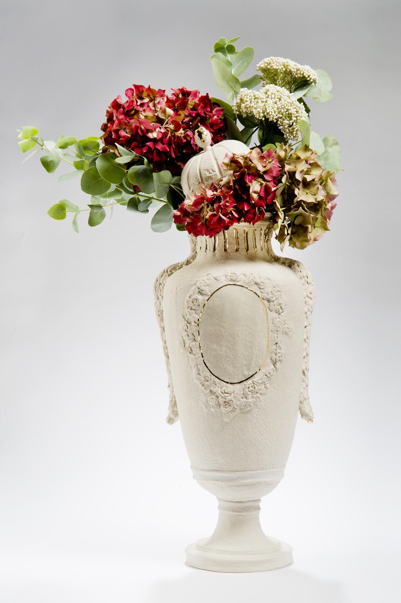 "<span class=""link fancybox-details-link""><a href=""/exhibitions/32/works/artworks73/"">View Detail Page</a></span><div class=""artist""><strong>Amy Hughes</strong></div><div class=""title""><em>Trésor Découvert Series; Lidded Earthstone Vase</em>, 2014</div><div class=""medium"">Hand built grogged stoneware body, transparent glaze with 22 carat gold lustre, parian cast flower additions</div><div class=""dimensions"">44 x 24 cm<br>17 3/8 x 9 1/2 in.</div>"