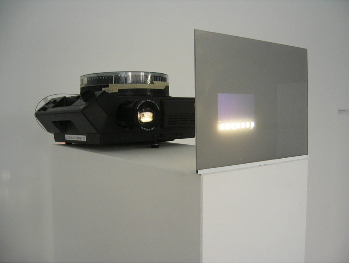 """<span class=""""link fancybox-details-link""""><a href=""""/exhibitions/109/works/artworks4782/"""">View Detail Page</a></span><div class=""""artist""""><strong> Anthony Mccall</strong></div><div class=""""title""""><em>Miniature in Black and White</em>, 1972</div><div class=""""signed_and_dated"""">work includes a signed and numbered certificate</div><div class=""""medium"""">81 slides, miniature Plexiglas screen, Kodak Carousel Projector. Continuous installation.</div><div class=""""dimensions"""">11 x 24 3/8 x 61 3/8 inches (28 x 62 x 156 cm)</div><div class=""""edition_details"""">ap</div>"""