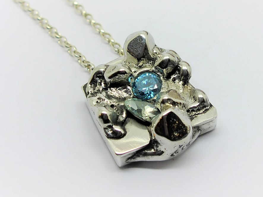 """<span class=""""link fancybox-details-link""""><a href=""""/artists/154-stacey-west/works/3938-stacey-west-found-treasures-pendant-small-2017/"""">View Detail Page</a></span><div class=""""artist""""><strong>Stacey West</strong></div> <div class=""""title""""><em>'Found Treasures' Pendant – small</em>, 2017</div> <div class=""""medium"""">Pewter and silver with aqua cubic zirconia on sterling silver chain</div><div class=""""copyright_line"""">Copyright The Artist</div>"""