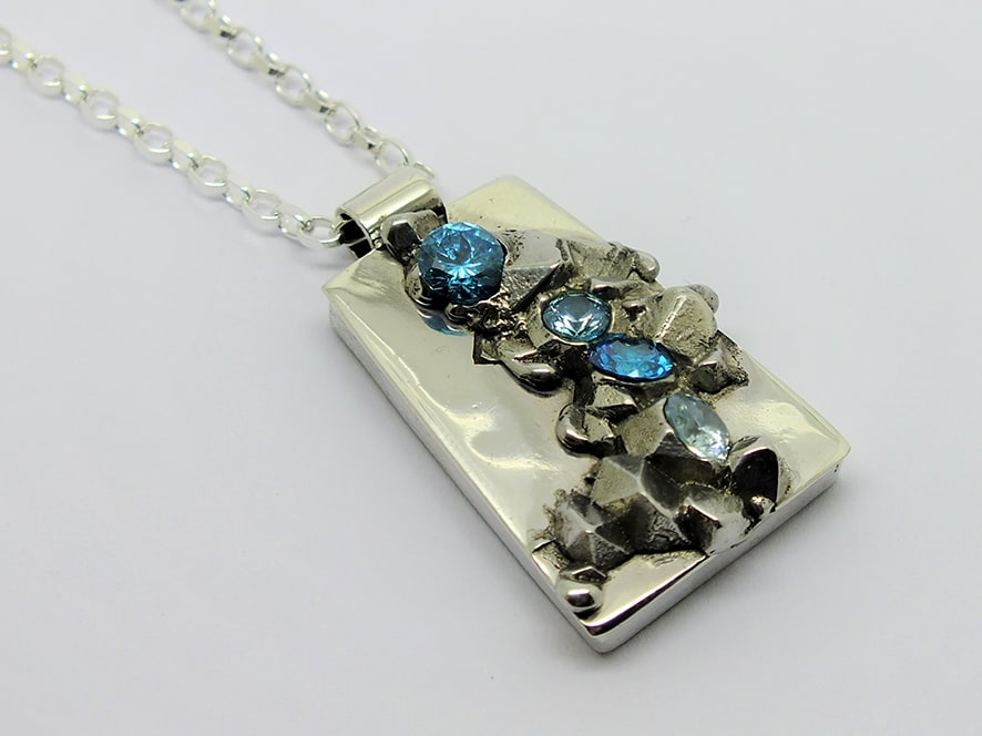 """<span class=""""link fancybox-details-link""""><a href=""""/artists/154-stacey-west/works/3940-stacey-west-found-treasures-pendant-large-2017/"""">View Detail Page</a></span><div class=""""artist""""><strong>Stacey West</strong></div> <div class=""""title""""><em>'Found Treasures' Pendant – large</em>, 2017</div> <div class=""""medium"""">Pewter and silver with aqua cubic zirconia on sterling silver chain</div><div class=""""copyright_line"""">Copyright The Artist</div>"""