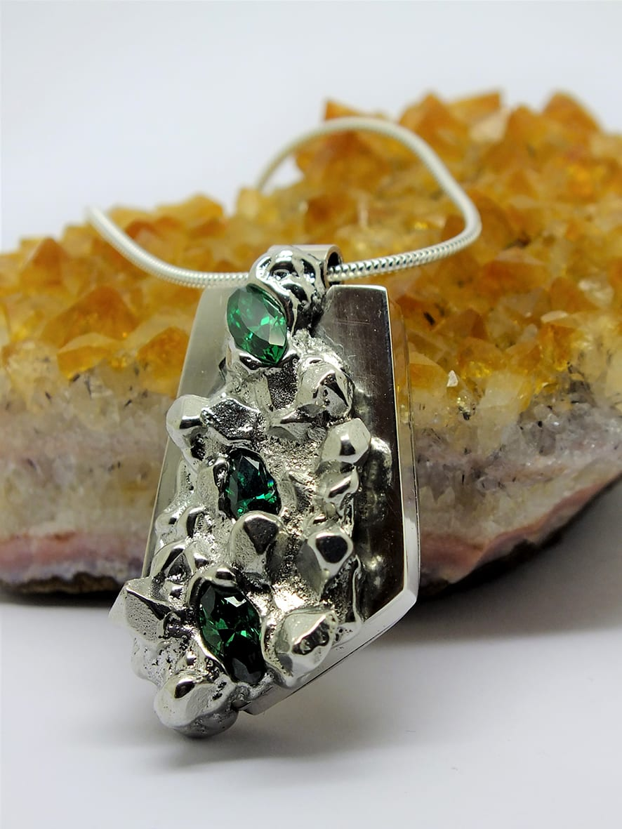 """<span class=""""link fancybox-details-link""""><a href=""""/artists/154-stacey-west/works/3945-stacey-west-found-treasure-pendant-large-2017/"""">View Detail Page</a></span><div class=""""artist""""><strong>Stacey West</strong></div> <div class=""""title""""><em>'Found Treasure' Pendant – large</em>, 2017</div> <div class=""""medium"""">Pewter and silver with green cubic zirconia on sterling silver chain</div><div class=""""copyright_line"""">Copyright The Artist</div>"""