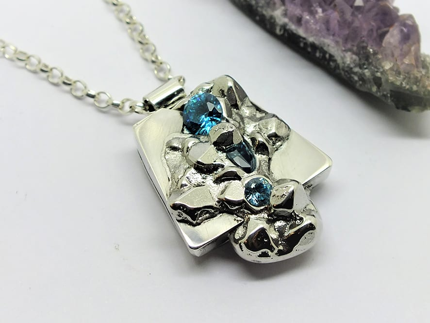 """<span class=""""link fancybox-details-link""""><a href=""""/artists/154-stacey-west/works/5093-stacey-west-found-treasures-pendant-large-2017/"""">View Detail Page</a></span><div class=""""artist""""><strong>Stacey West</strong></div> <div class=""""title""""><em>'Found Treasures' Pendant – large</em>, 2017</div> <div class=""""medium"""">Pewter and silver with aqua cubic zirconia on sterling silver 18 """"chain</div><div class=""""price"""">£145.00</div><div class=""""copyright_line"""">Copyright The Artist</div>"""